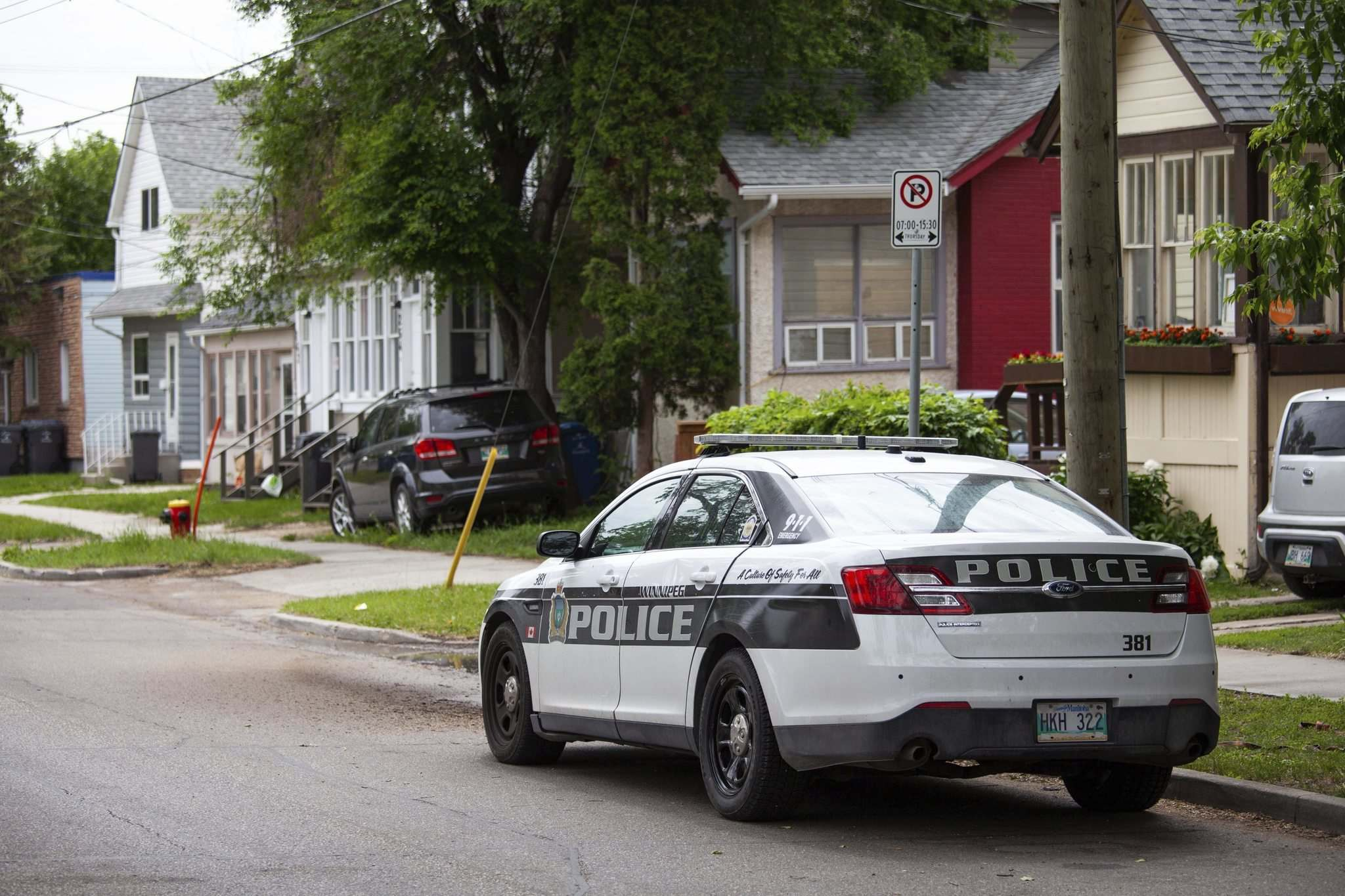 A police cruiser is parked on Burrows avenue near the spot where a 12-year-old youth was killed on June 19. (Daniel Crump / Winnipeg Free Press files)