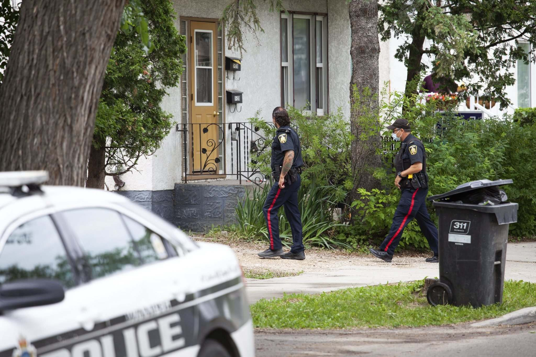 Police officers canvas the 200 block of Burrows Avenue after a 12-year-old youth was fatally stabbed Friday evening. (Daniel Crump / Winnipeg Free Press)</p>