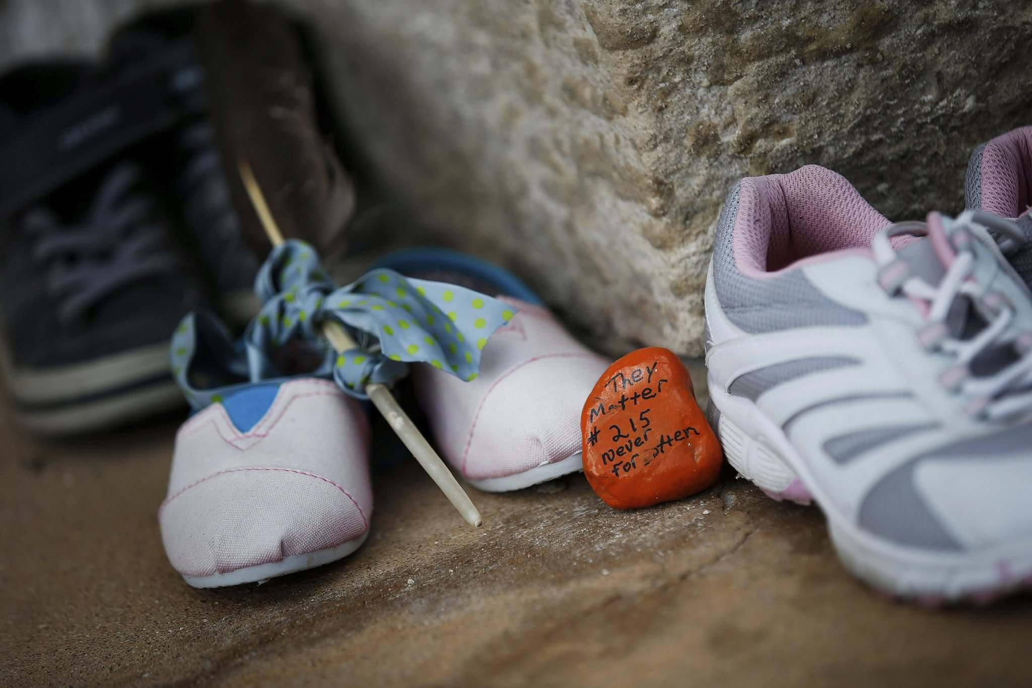 Shoes placed on the steps of the Assiniboia Indian Residential School in River Heights to commemorate the 215 Indigenous children found in unmarked graves in B.C. earlier this year. </p>