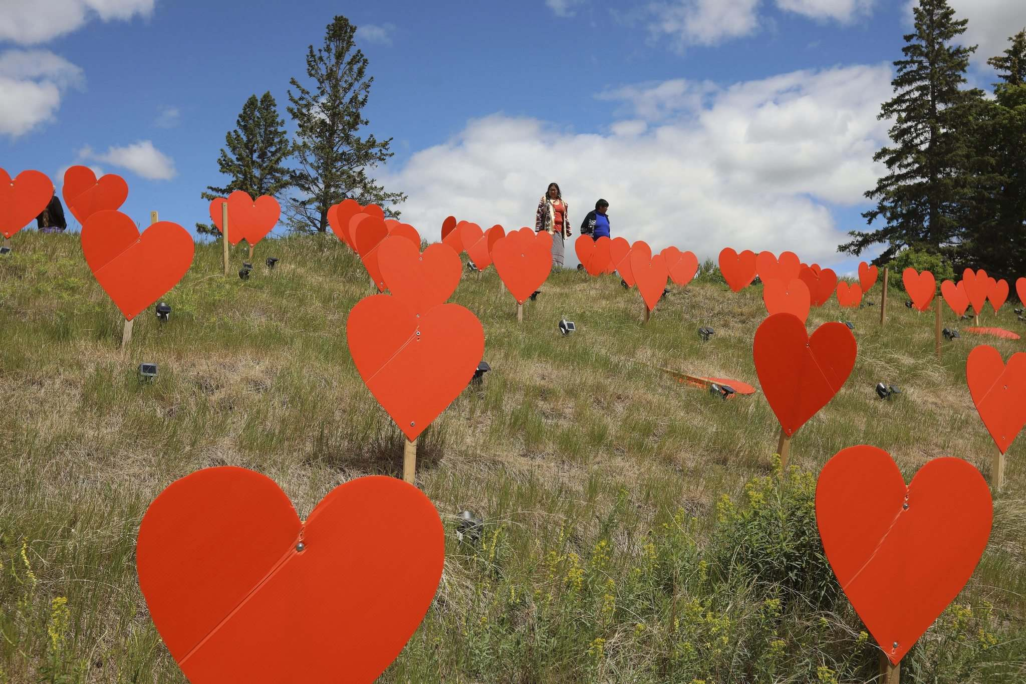 Tim Smith / The Brandon Sun</p><p>Guests look over the orange hearts placed on the site of the former Brandon Indian Residential School, symbolizing the 104 children who died at the institution.</p>