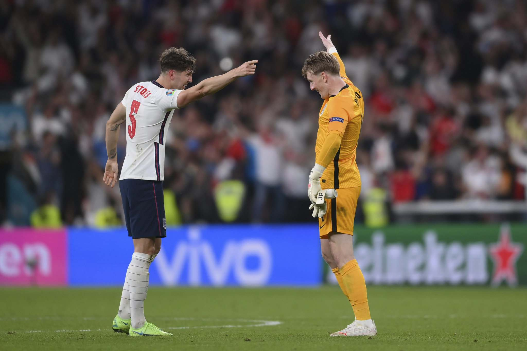 England's goalkeeper Jordan Pickford, right, celebrates with his teammate John Stones at the end of the Euro 2020 soccer semifinal match between England and Denmark.
