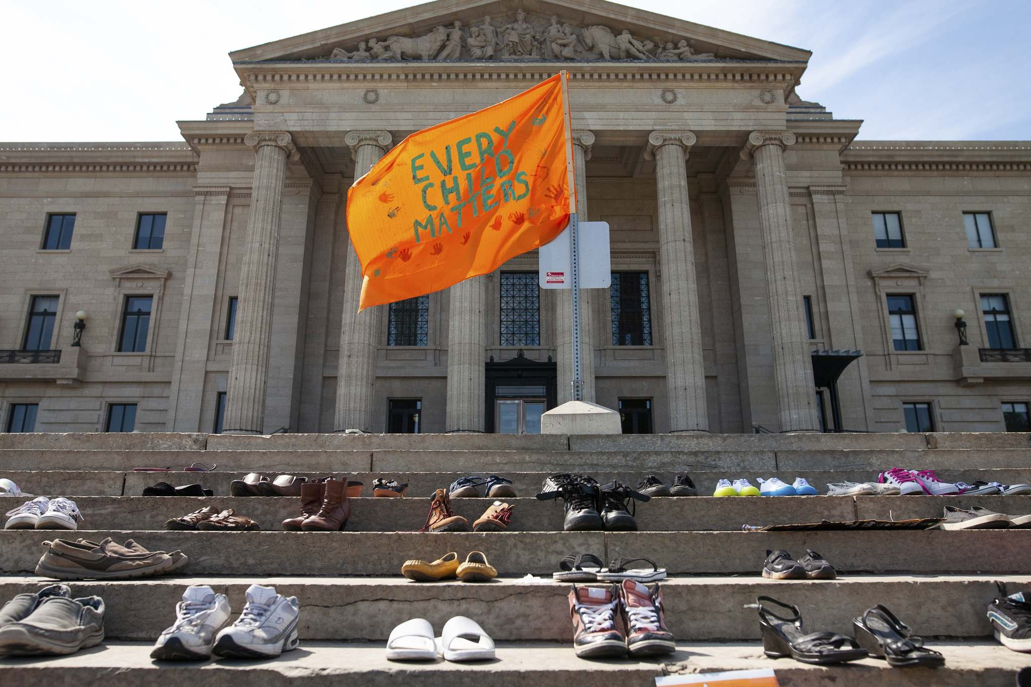 Daniel Crump / Winnipeg Free Press</p><p>An orange flag flies above shoes that have been placed on the steps of the Manitoba legislature.</p>