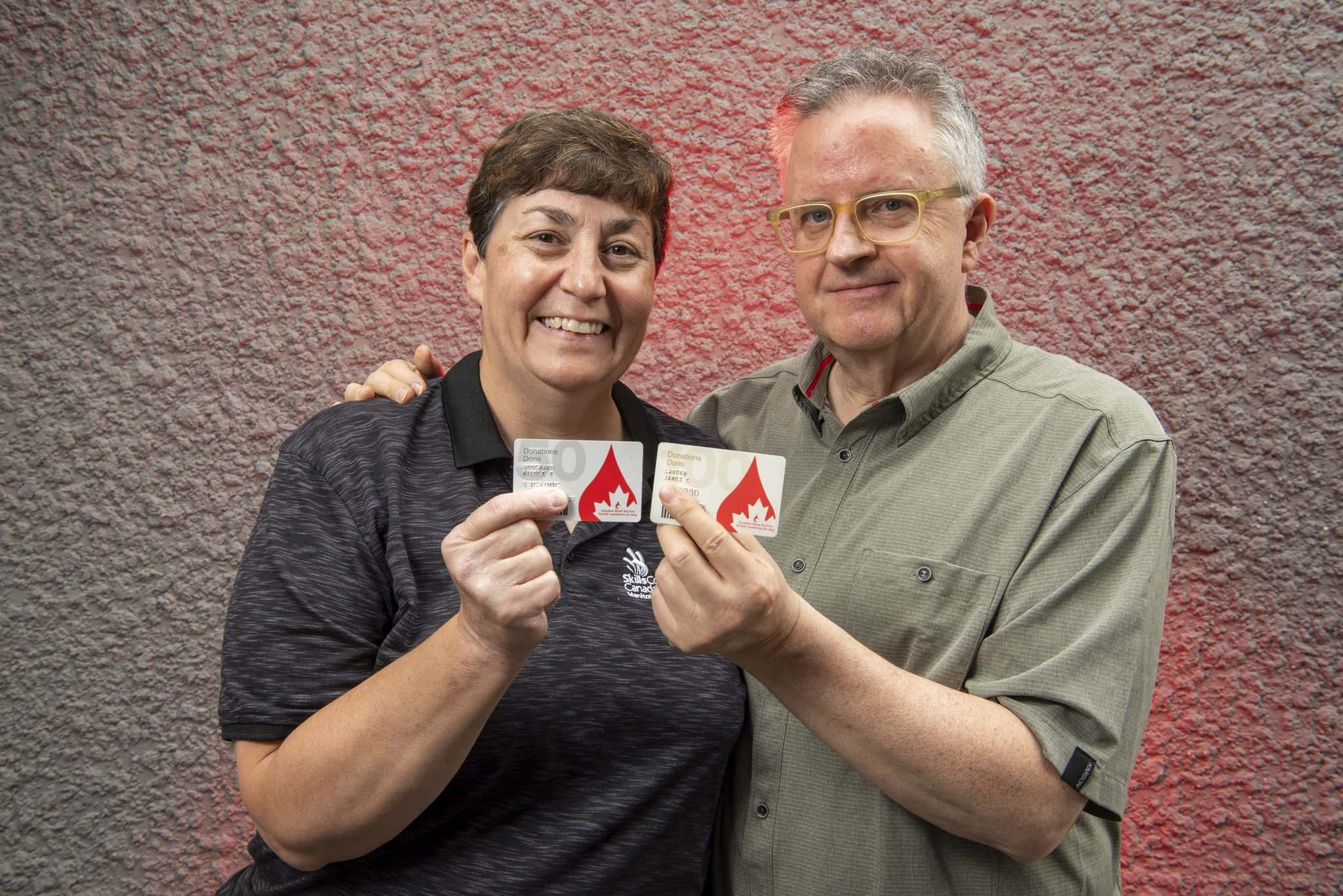 Nicole Bouchard and Carey Lauder display their donation cards. Both are longtime blood donors, with Bouchard at 75 donations and Lauder at 130 donations. (Alex Lupul / Winnipeg Free Press)