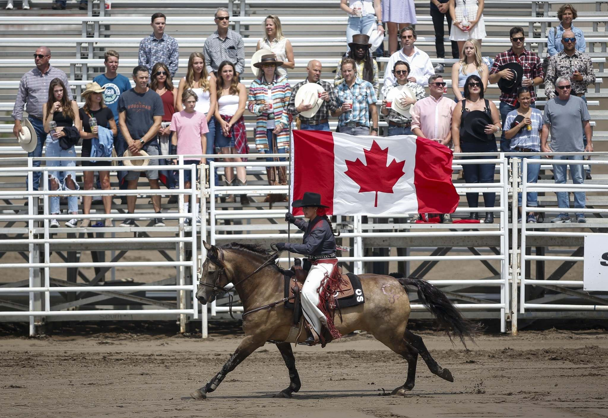 Jeff McIntosh / The Canadian Press</p><p>A rider carries the Canadian flag during the national anthem before the start of rodeo action at the Calgary Stampede.