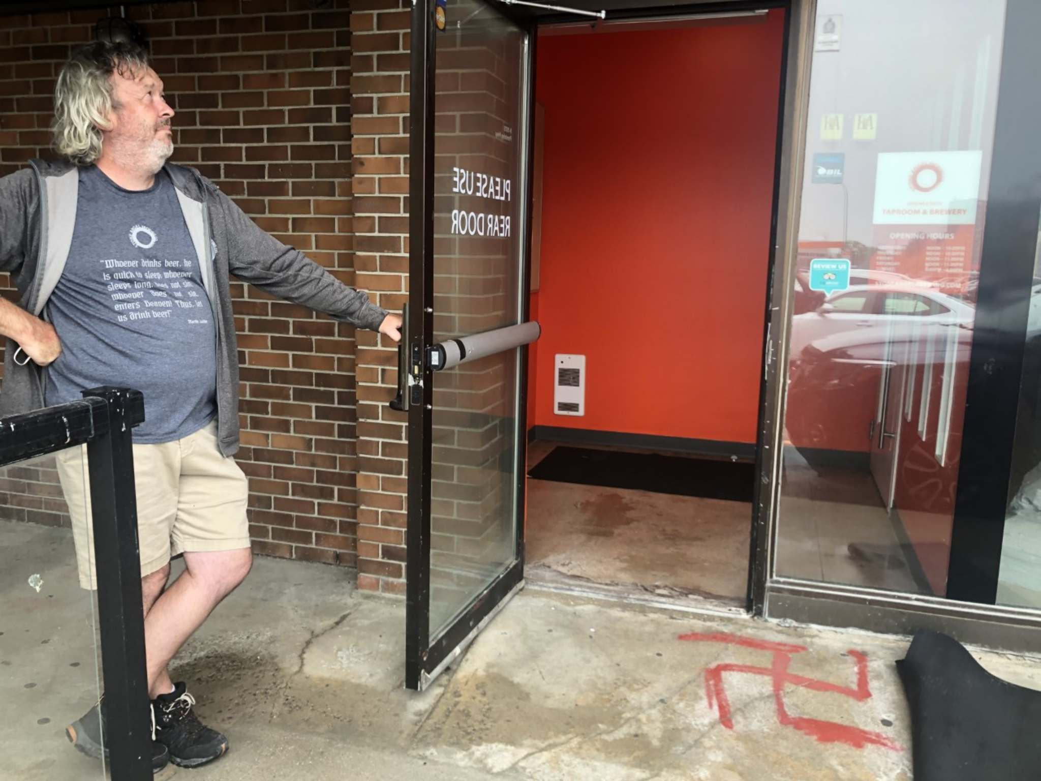 Stone Angel Brewing co-owner Paul Clerkin surveys the damage after his business and others were vandalized with hateful graffiti overnight. (Erik Pindera / Winnipeg Free Press)