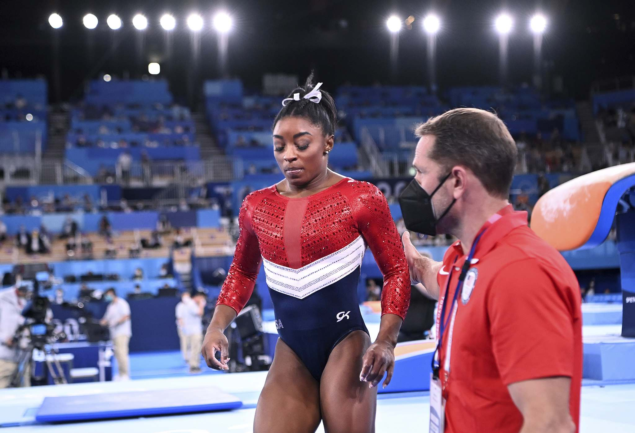 U.S. gymnast Simone Biles is consoled after competing on the vault and withdrawing from competition due to an injury in the women's team final at the 2020 Tokyo Olympics on Tuesday, in Tokyo, Japan.