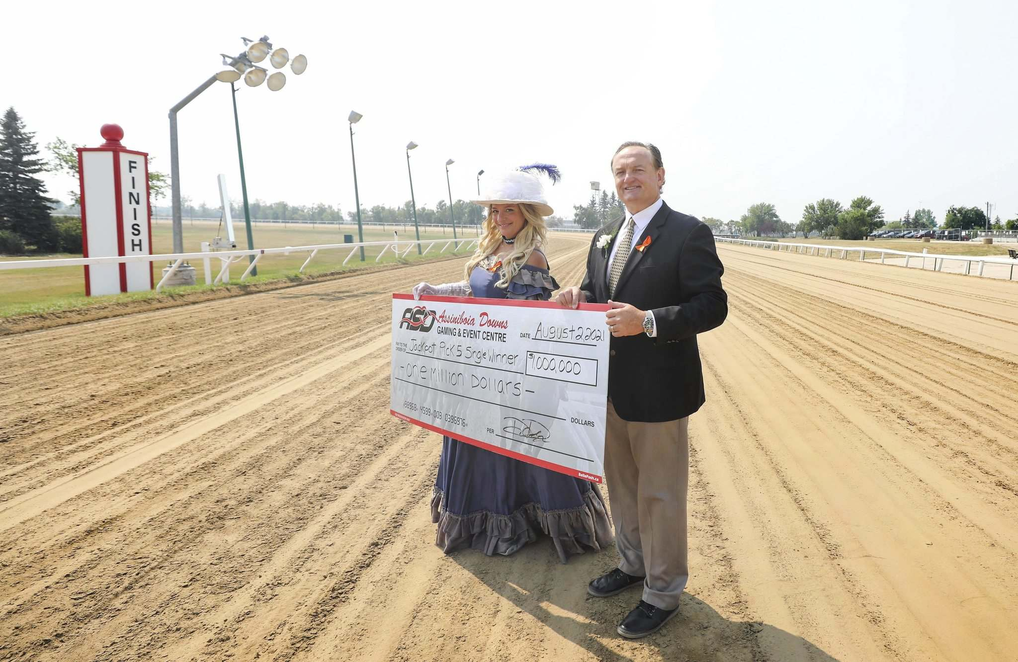 RUTH BONNEVILLE / WINNIPEG FREE PRESS</p><p>Assiniboia Downs CEO Darren Dunn and Francine Fournier with a giant cheque representing the big bucks to be won Monday at the Manitoba Derby.</p>
