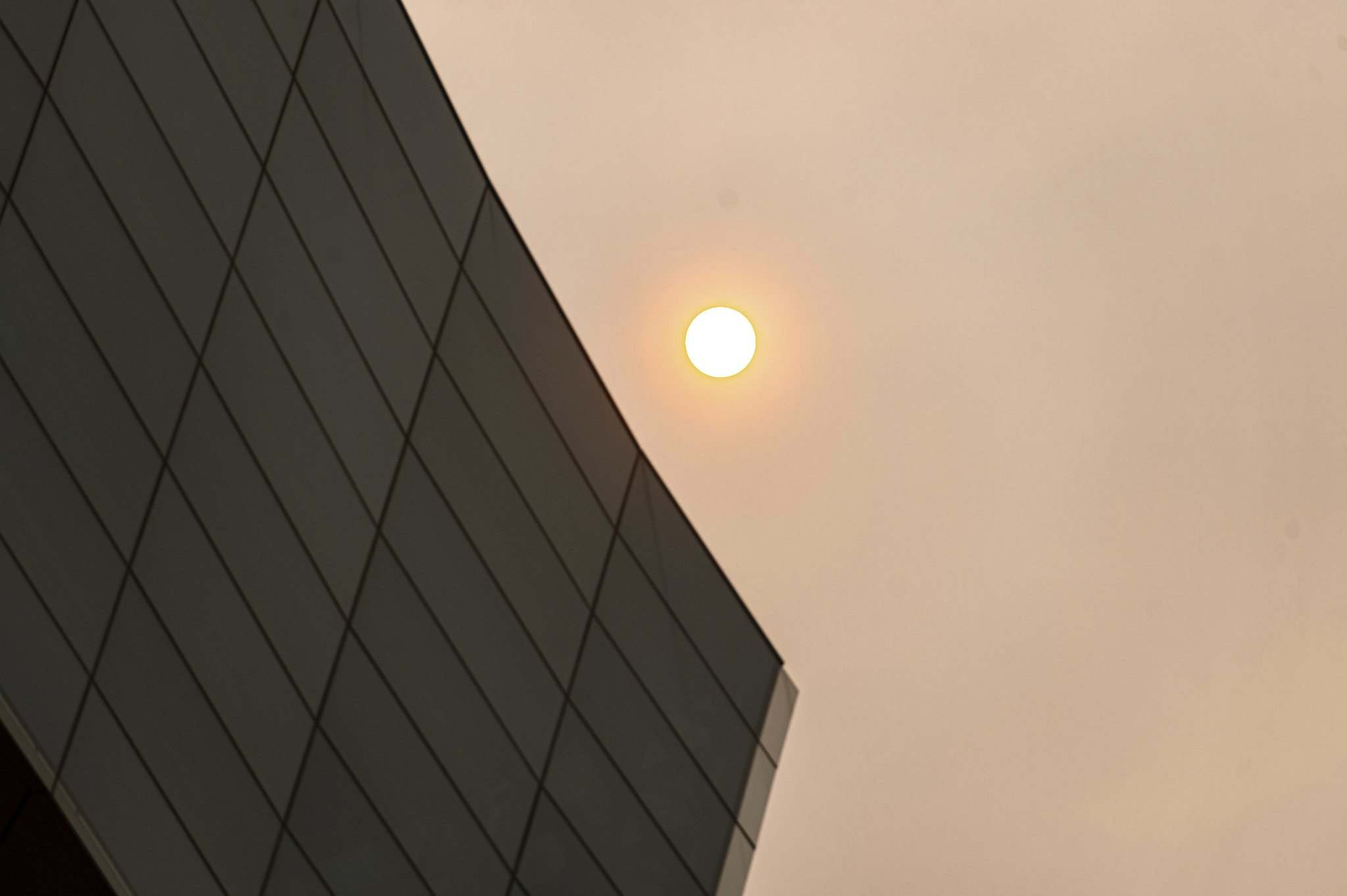 The sun glows red behind a smoke filled sky behind the Canadian Museum for Human Rights Saturday morning. (Mike Sudoma / Winnipeg Free Press)</p>