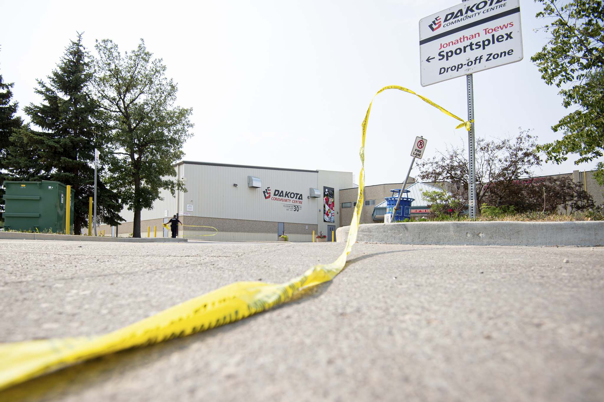Police tape hangs from a sign in the parking lot of the Dakota Community Centre Friday afternoon. A 19-year-old man is recovering in hospital from a gunshot wound sustained from the early Friday morning incident. Two teens are in custody, and an 18-year-old remained at large Saturday. (Mike Sudoma / WInnipeg Free Press)</p>