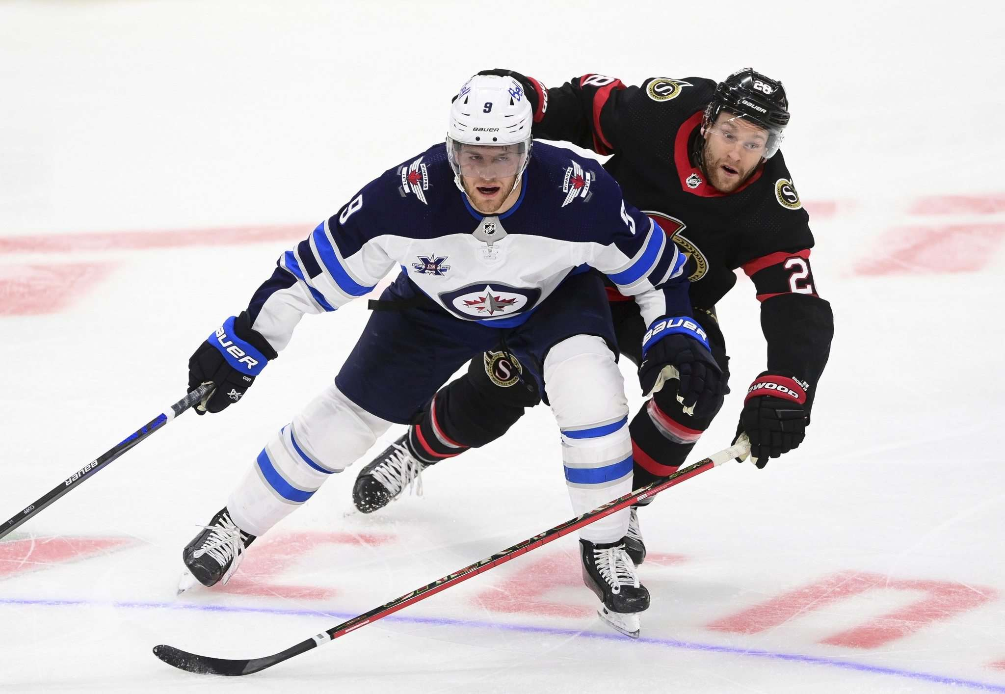 Jets GM Kevin Cheveldayoff is in a tough spot when it comes to negotiating a deal with versatile forward Andrew Copp (left) and remaining under the NHL's salary cap. (Sean Kilpatrick / The Canadian Press files)