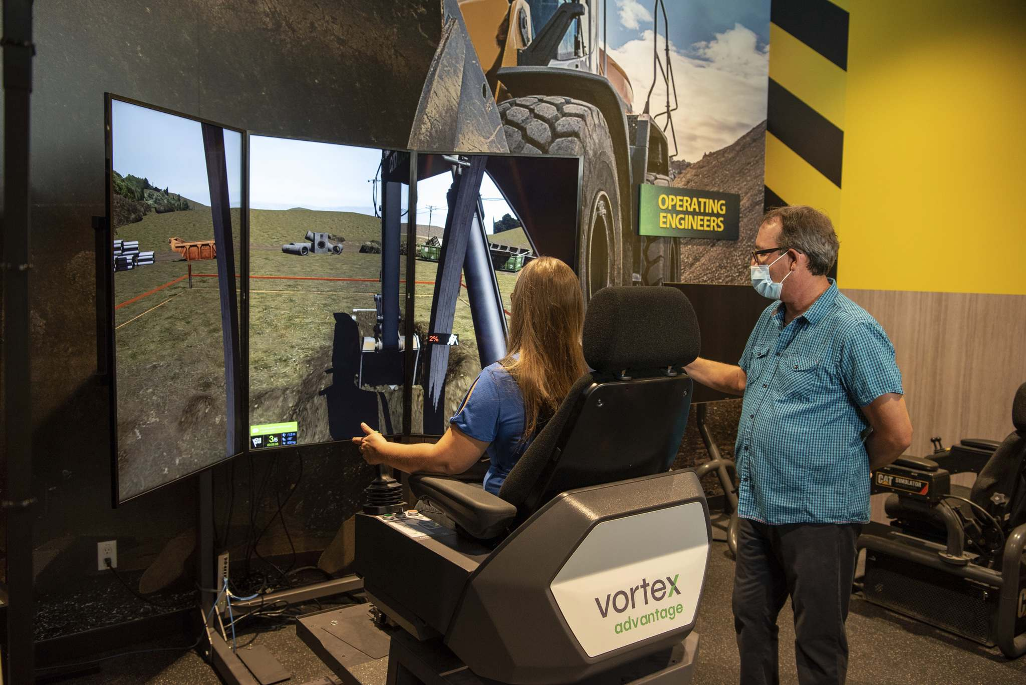 ALEX LUPUL / WINNIPEG FREE PRESS</p><p>Ron Armstrong, training and curriculum manager, instructs Debby Raill how to operate machinery in the new Manitoba Building Trades Institute's Try The Trades exhibition hall on Wednesday.</p>