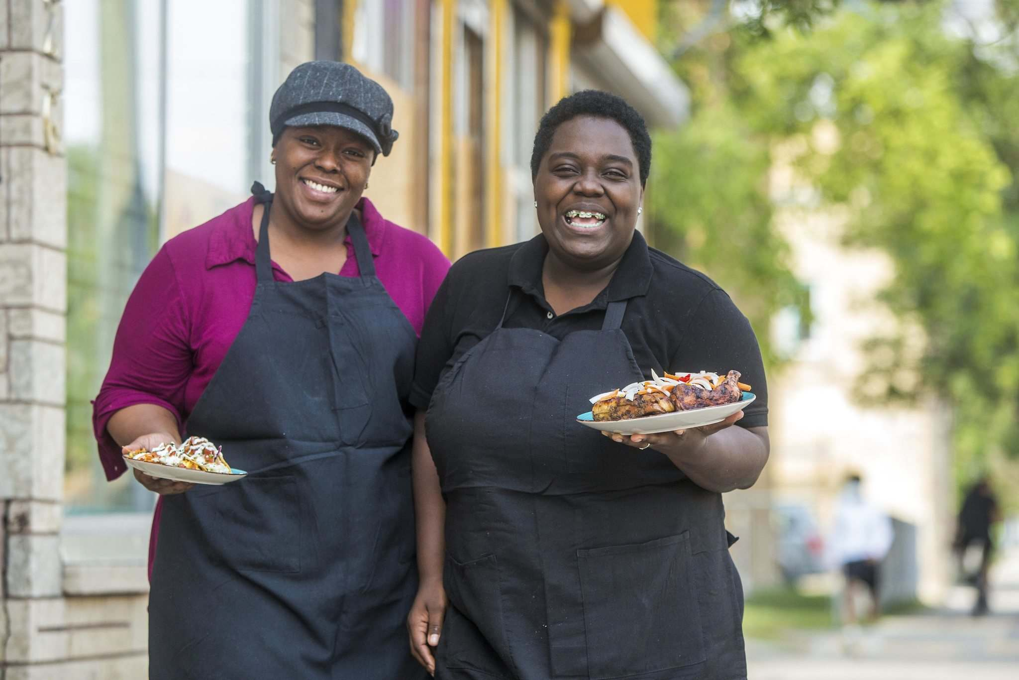 Deidré Coleman (left) and Patrice Gilman are taking part in this month's Black History Manitoba block party, dishing up Caribbean food from their West End restaurant. (Mikaela MacKenzie / Winnipeg Free Press)</p>