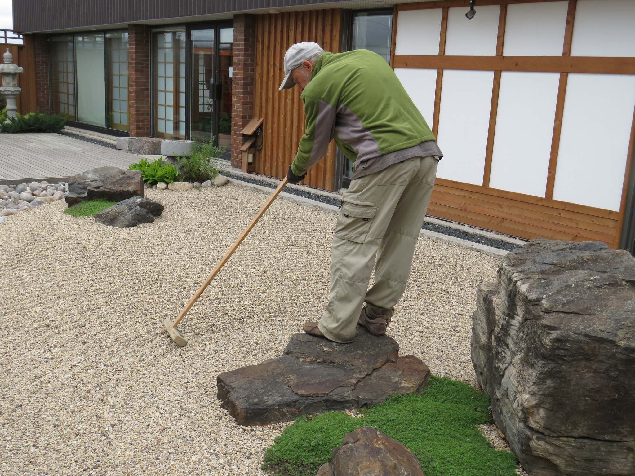 <p>Colleen Zacharias / Winnipeg Free Press</p><p>Raymond Normandeau, niwashi, uses a wooden rake to create meditative patterns in the gravel at the Japanese garden at 180 McPhillips St.</p>