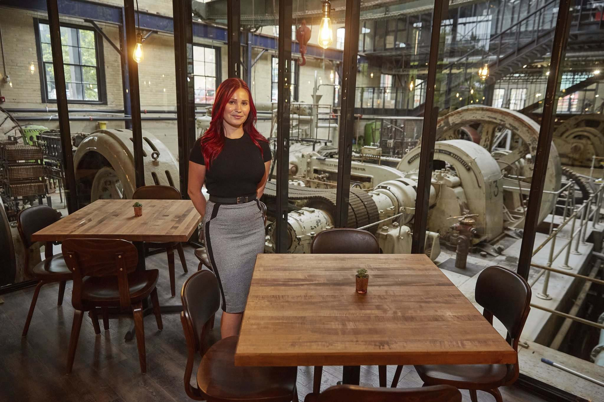 MIKE DEAL / WINNIPEG FREE PRESS</p><p>General Manager Kaitlin Nikkel at one of the tables that look out onto the preserved area of the pumphouse.</p></p>
