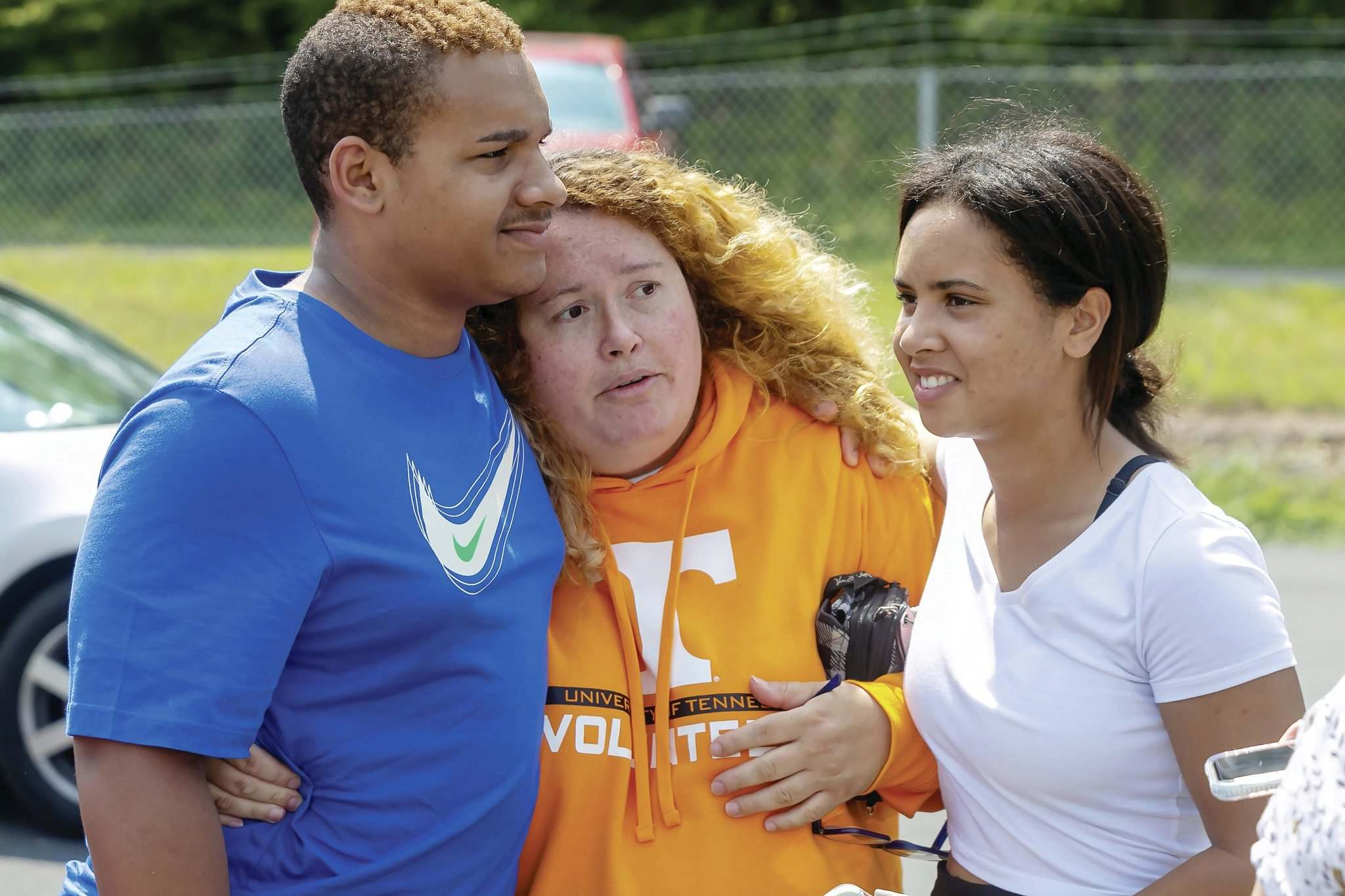 Rhonda Lawson (centre) hugs her children, Donovan and Madison, as she describes to local media the moment she received the phone call of a possible active shooter at Volunteer High School in Church Hill, Tenn., on Aug. 10. (Larry N. Souders / The Associated Press files)