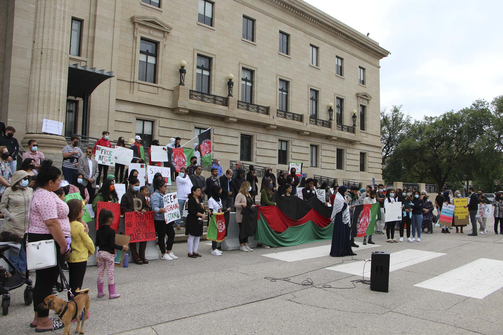 Protesters gather at the steps of the Manitoba Legislature on Aug. 28, calling Ottawa to send more help for Afghans who want to flee Afghanistan since the Taliban have taken over the country. (Gabrielle Piche / Winnipeg Free Press)</p>