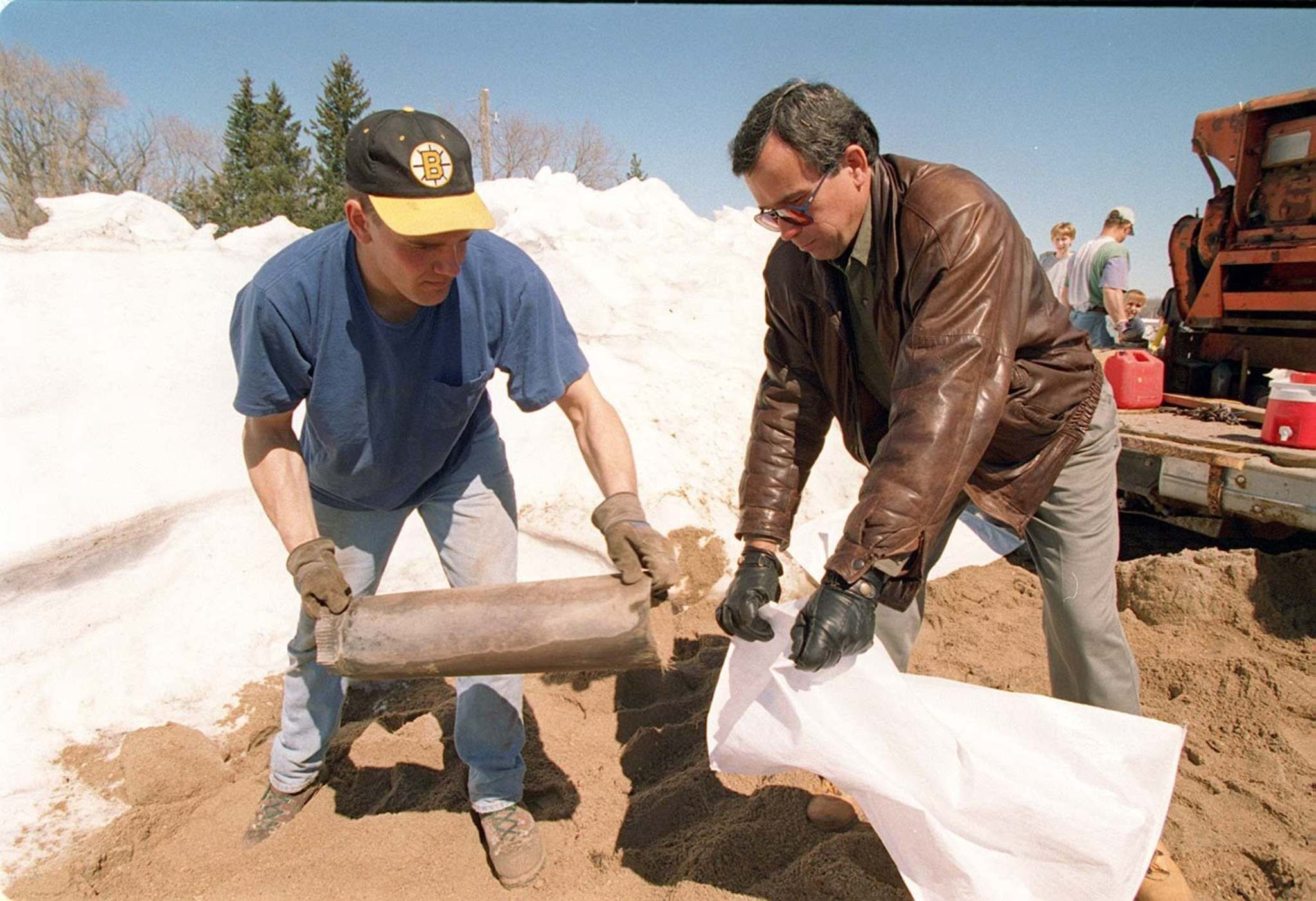 Gary Filmon (right) helps build a sandbag dike at an Emerson-area farm in 1997. Filmon calls the Flood of the Century the greatest challenge he faced as Manitoba's premier. (Jeff De Booy / Winnipeg Free Press files)