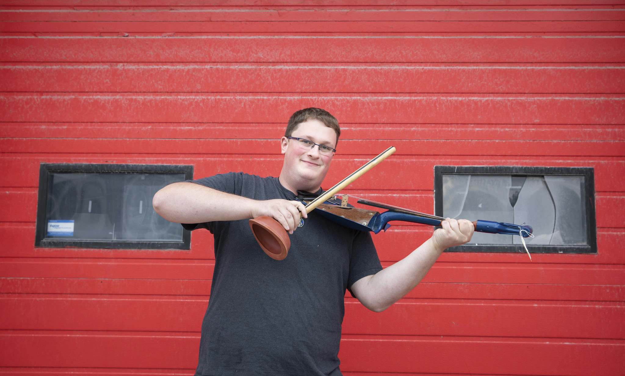 Jared Warkentin, assistant at St. Vital Museum, with a bow and fiddle made from a toilet plunger and shovel. (Jessica Lee / Winnipeg Free Press)</p>