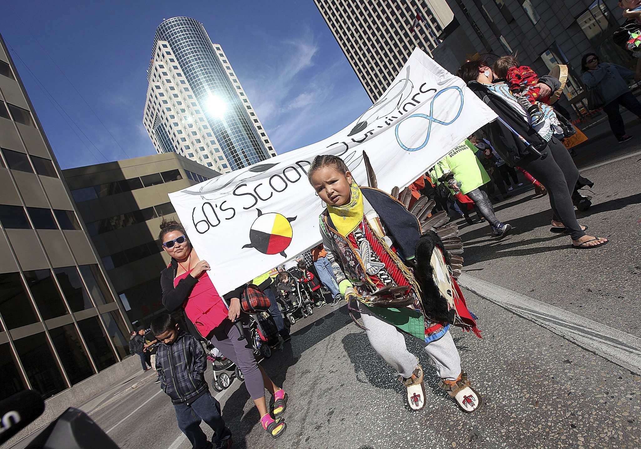 "PHIL HOSSACK / WINNIPEG FREE PRESS</p><p>Harley Bird, 5, leads participants up Main Street in a rally and march to the Manitoba Legislative Building on Friday to draw attention to the ""60's Scoop.""</p>"