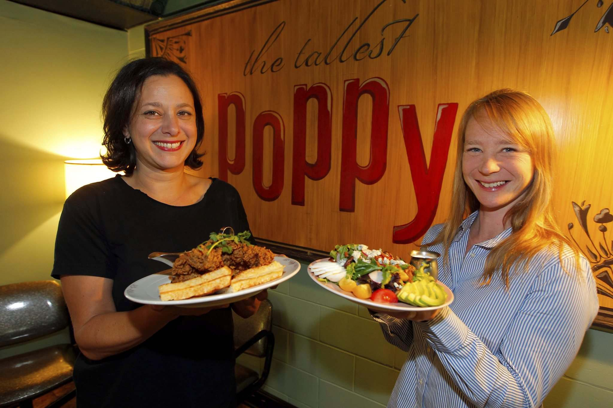 BORIS MINKEVICH / WINNIPEG FREE PRESS</p><p>The Tallest Poppy owner Talia Syrie with fried chicken and waffles; manager Eileen Fowler shows off the Cobb salad.</p></p>