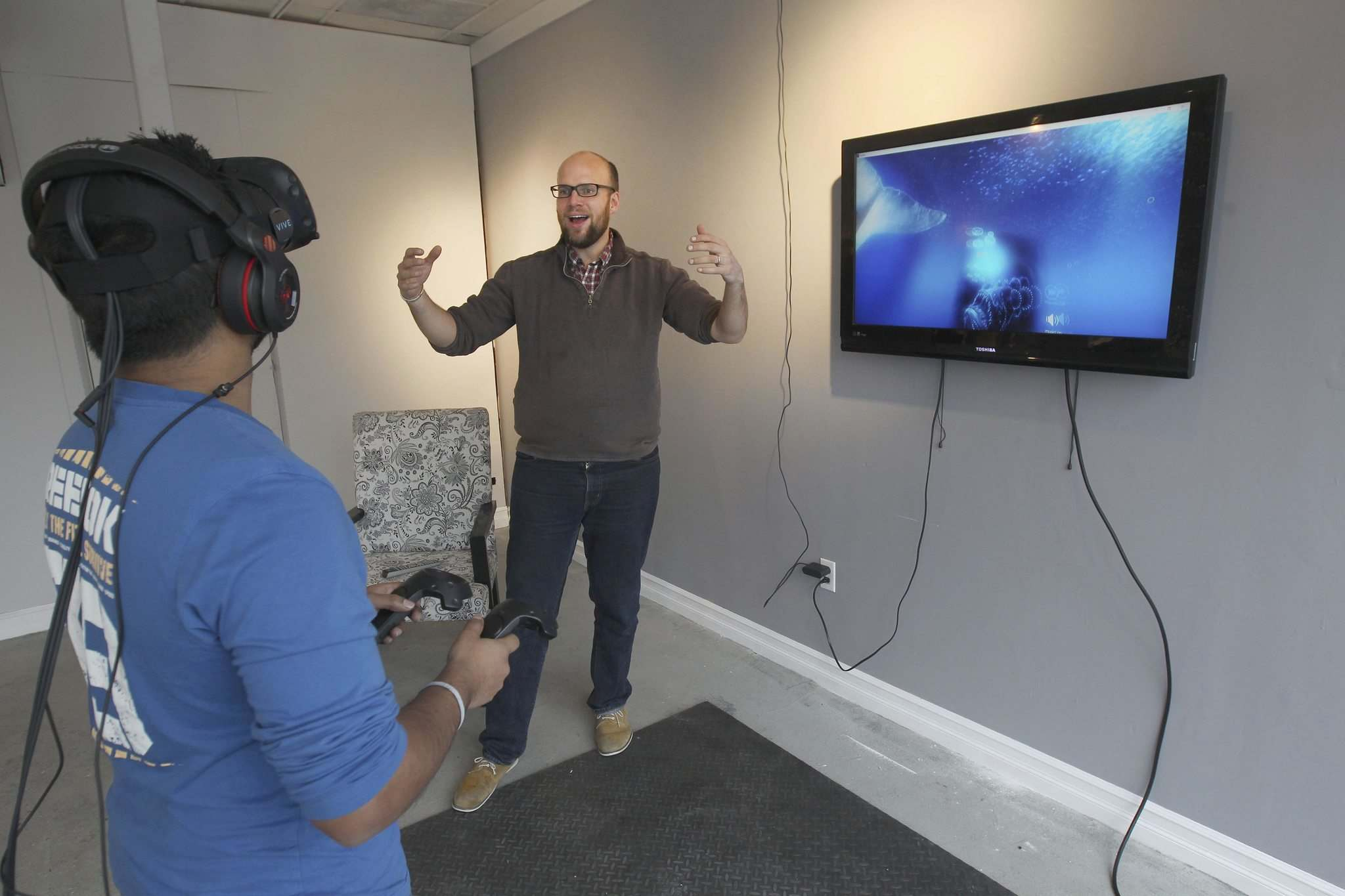 JOE BRYKSA / WINNIPEG FREE PRESS</p><p>Charith Jayawardana, Left, tries out Winnipeg's first Virtual Reality Arcade at The Portal with the help of owner Chris Hall.</p>