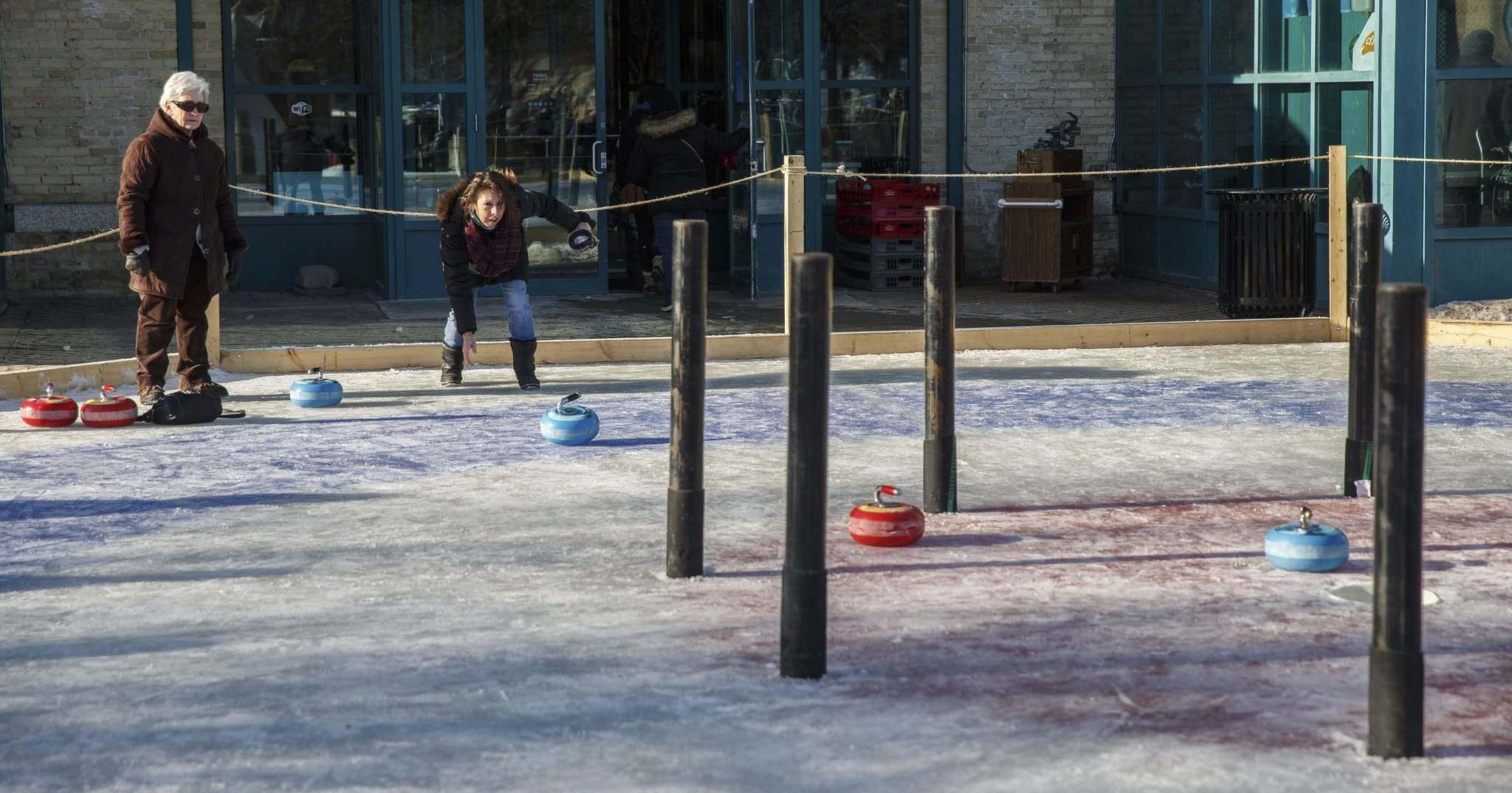 Lorene Giasson throws a curling rock while playing Crokicurl with her friend Rosa Conrad (left).