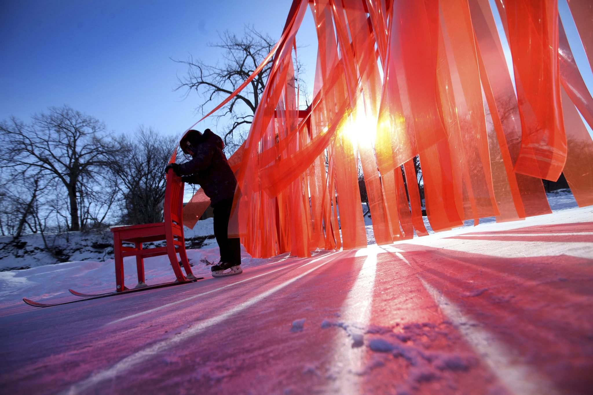 <p>Ethan Offman, age 9, pushes a kicksled through the Open Border warming hut, a wall made out of orange plastic strips hanging across the river trail along the Assiniboine River.</p>