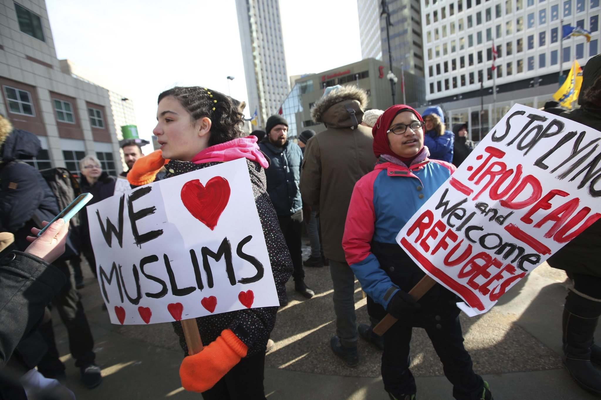 <p>Young tweens, Leen (left) and her friend Isra hold signs and speak out at ralliy Friday.</p>