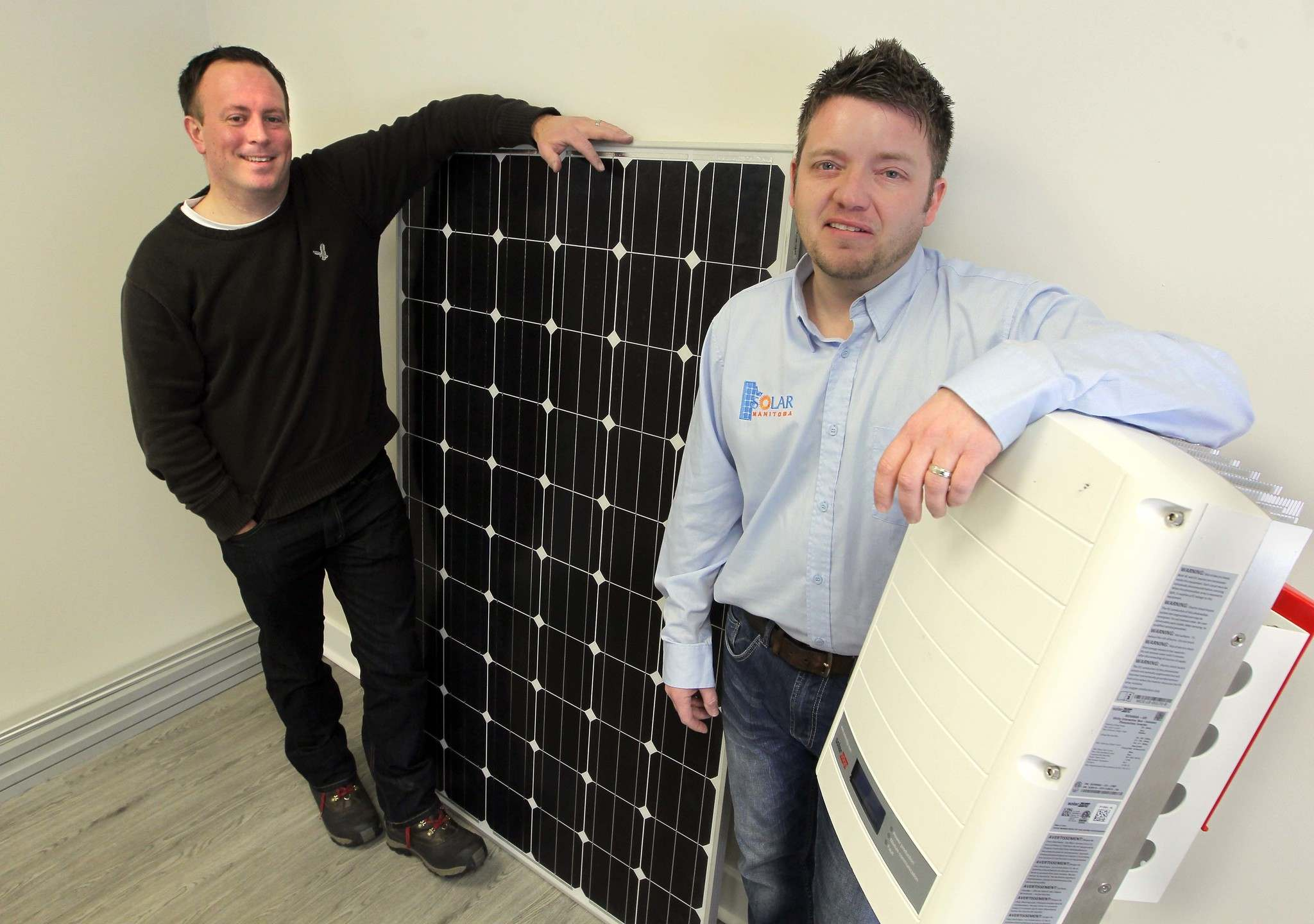 Alex Stuart, left, and Justin Phillips, co-founders of Sycamore Energy, pose with a solar panel system.</p>
