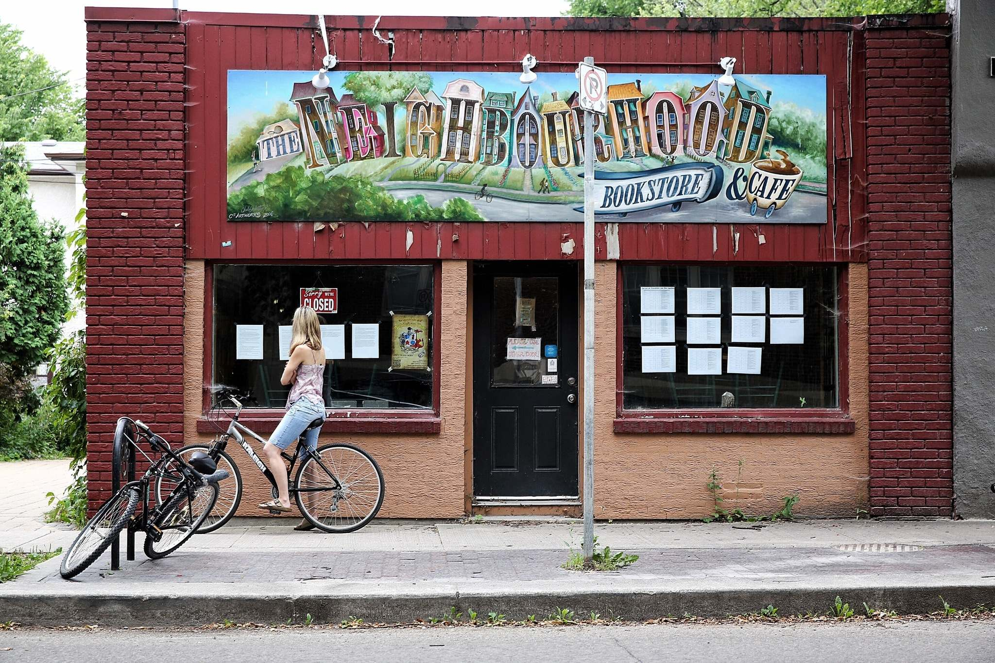 MIKE DEAL / WINNIPEG FREE PRESS FILES</p><p>A cyclist reads the notice taped to the window of The Neighbourhood Cafe outlining the reason it is closed in August. The cafe reopened in December after city hall granted an exemption to the grease trap requirement -- but only on condition that all food and drinks be served in disposable plastic.</p>