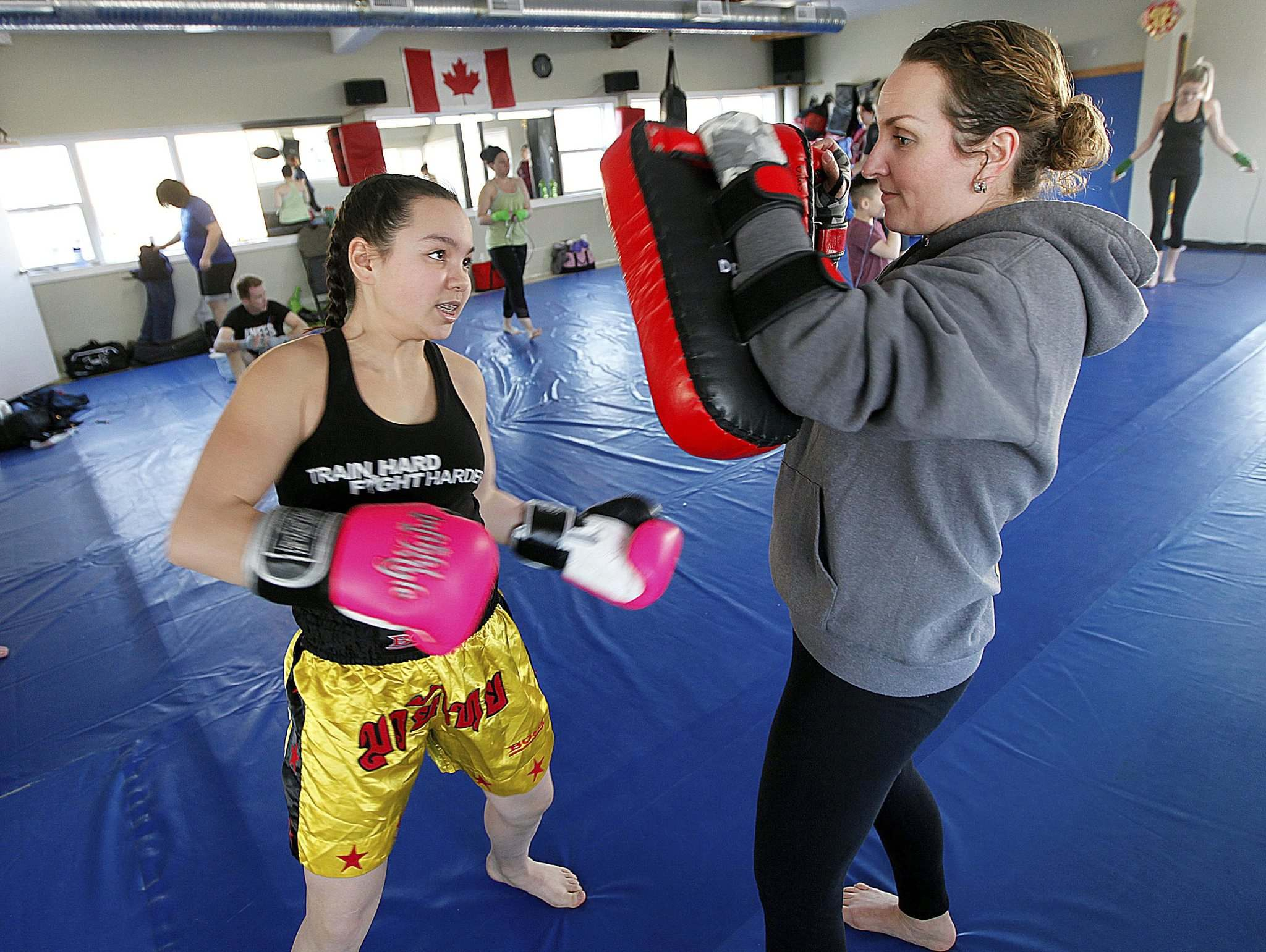 PHIL HOSSACK / WINNIPEG FREE PRESS</p><p>Jenelle Vincent-Oasis hold the pads while her daughter Jada, 11, delivers a series of punches and kicks during warm-up.</p>