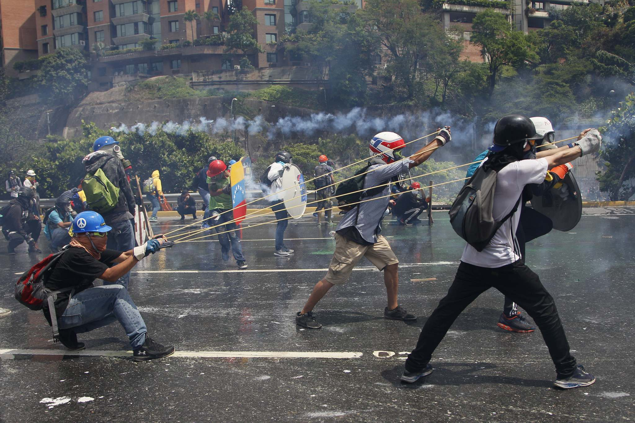 ARIANA CUBILLOS / THE ASSOCIATED PRESS FILES</p><p>Anti-government protesters aim a giant slingshot holding a bottle of fecal matter at security forces blocking their march from reaching the Supreme Court in Caracas.</p>