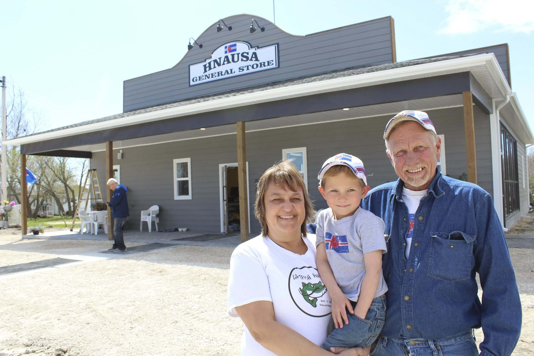 </p><p>Hnausa General Store owners Donna and Brian Austfjord hold their five-year-old grandson, Deegan Knutson, at the store's soft opening on May 12.</p></p>