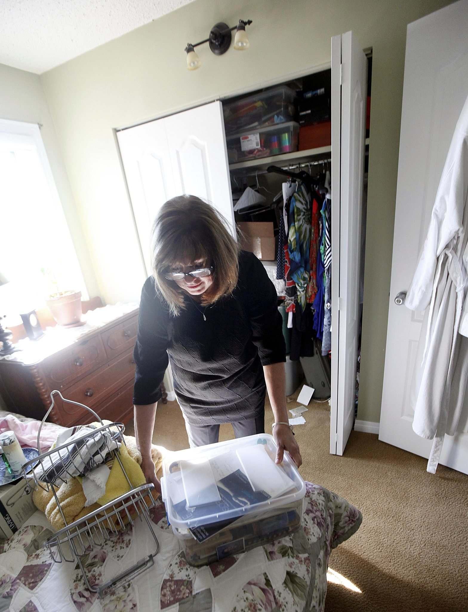 <p>Anne Oake pulls a tupperware container full of her son Bruce's memorabilia from a bedroom closet. (Phil Hossack / Winnipeg Free Press)</p>