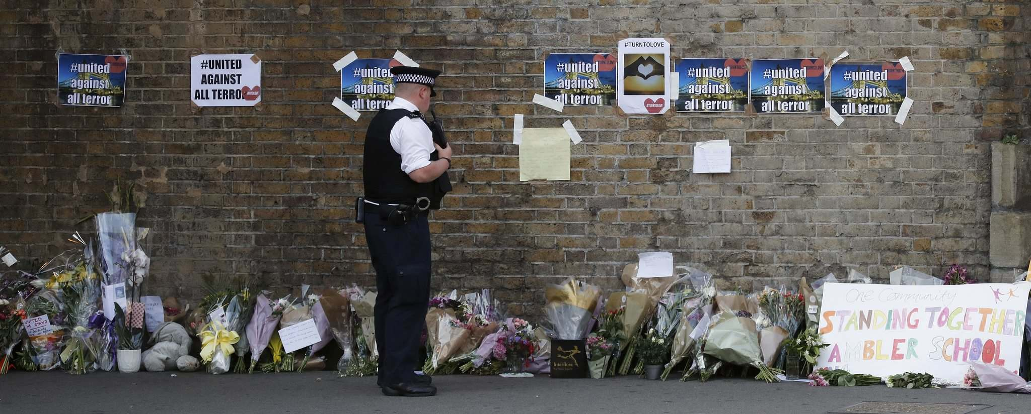 Frank Augstein / The Associated Press</p><p>A police officer stands near floral tributes in Finsbury Park in north London where a man behind the wheel of a van drove into worshippers near the Muslim Welfare House mosque on Monday, sending nine to hospital.</p>