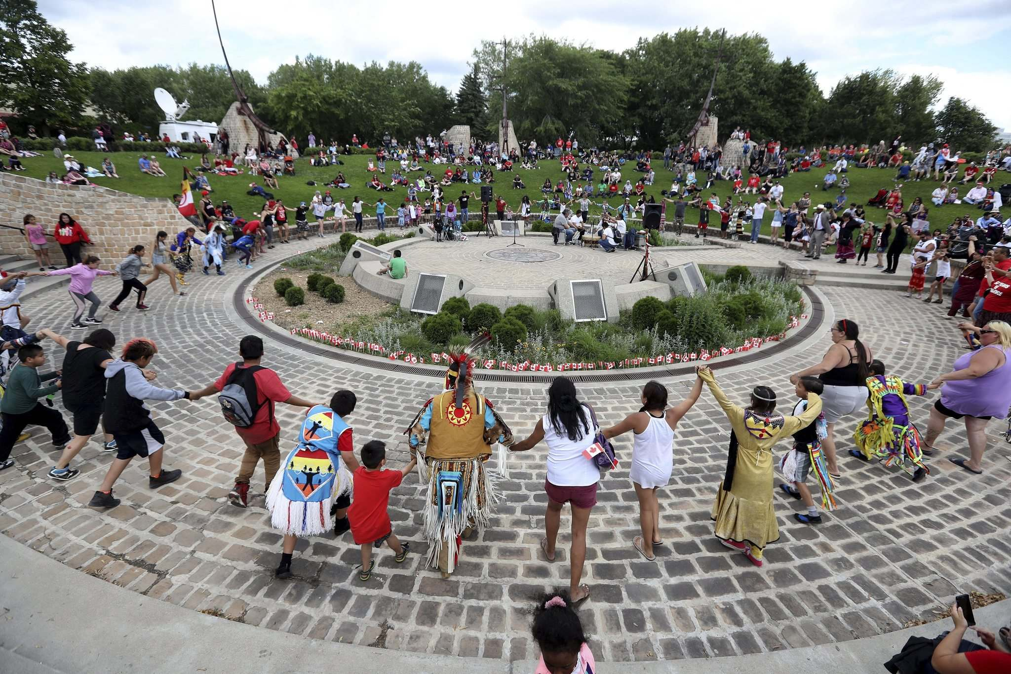 TREVOR HAGAN / WINNIPEG FREE PRESS</p><p>A crowd dances around drummers in the Oodena Celebration Circle during Canada Day festivities Saturday at The Forks.</p>