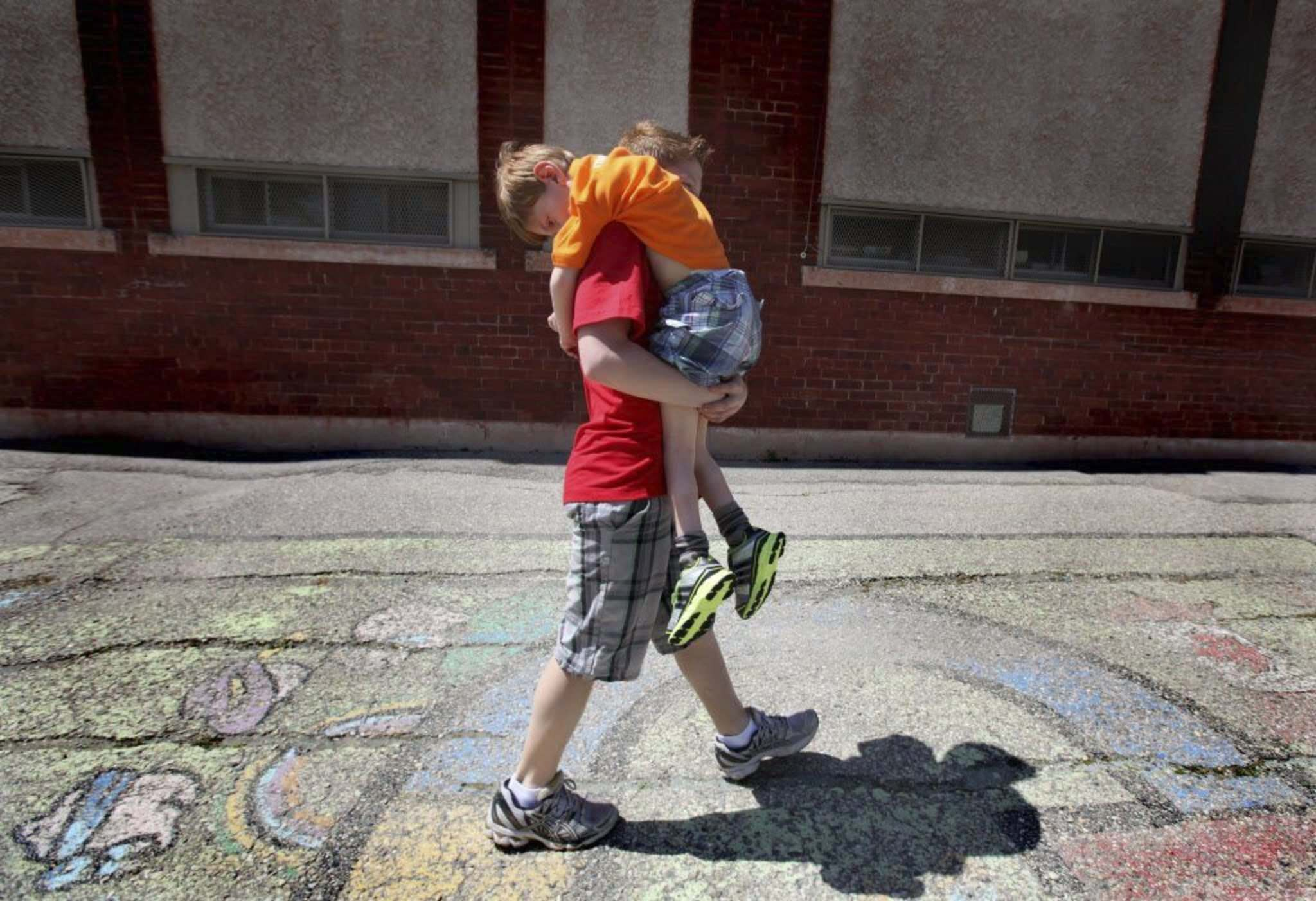 He ain&#39;t heavy; he&#39;s my brother: in 2012, Griffin, 12, carries Tyler, 7, to the play structure at Windsor School.</p>Ruth Bonneville / Winnipeg Free Press</p>