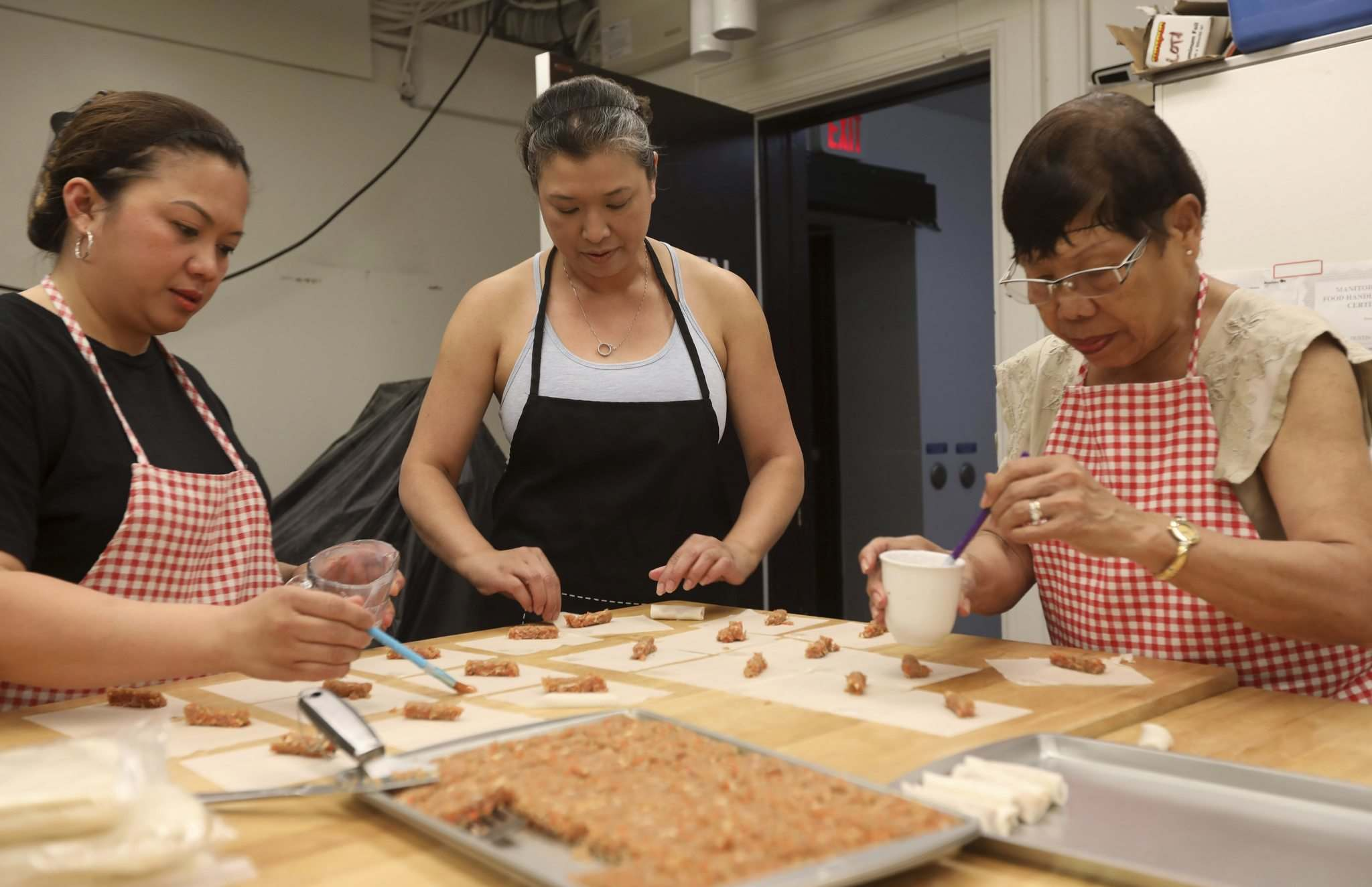 Lulu (centre) makes her rolls with her friend Heidee Bautista (left) and mother Norma Lulu (right) in the Knox United Church kitchen, but will be moving to her own store next month. (Ruth Bonneville / Winnipeg Free Press)</p>