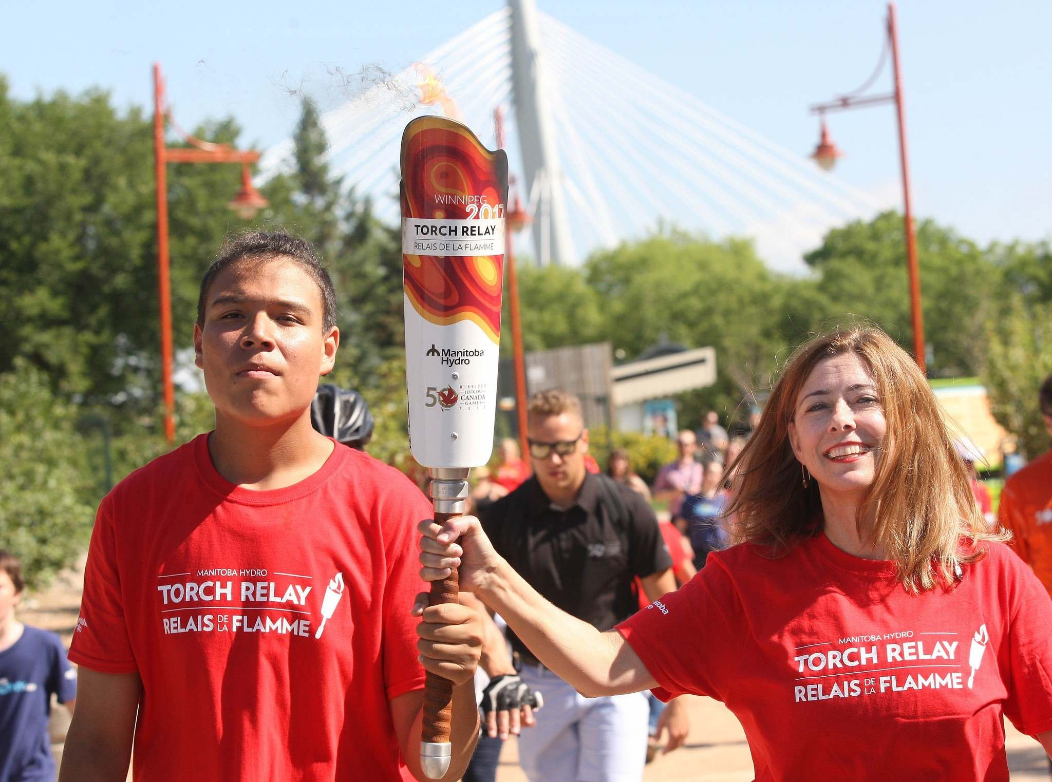 Jason Pruden (right) and Shannon Prud-Homme carry the Canada Games torch at The Forks. Jason, 14, was evacuated from his Lake St. Martin First Nation home due to flooding six years ago. Prud-Homme, a family doctor from Treherne, carried the torch for Fit Kids, Healthy Kids, an organziation sponsored by Doctors Manitoba. (Joe Bryksa / Winnipeg Free Press)</p>