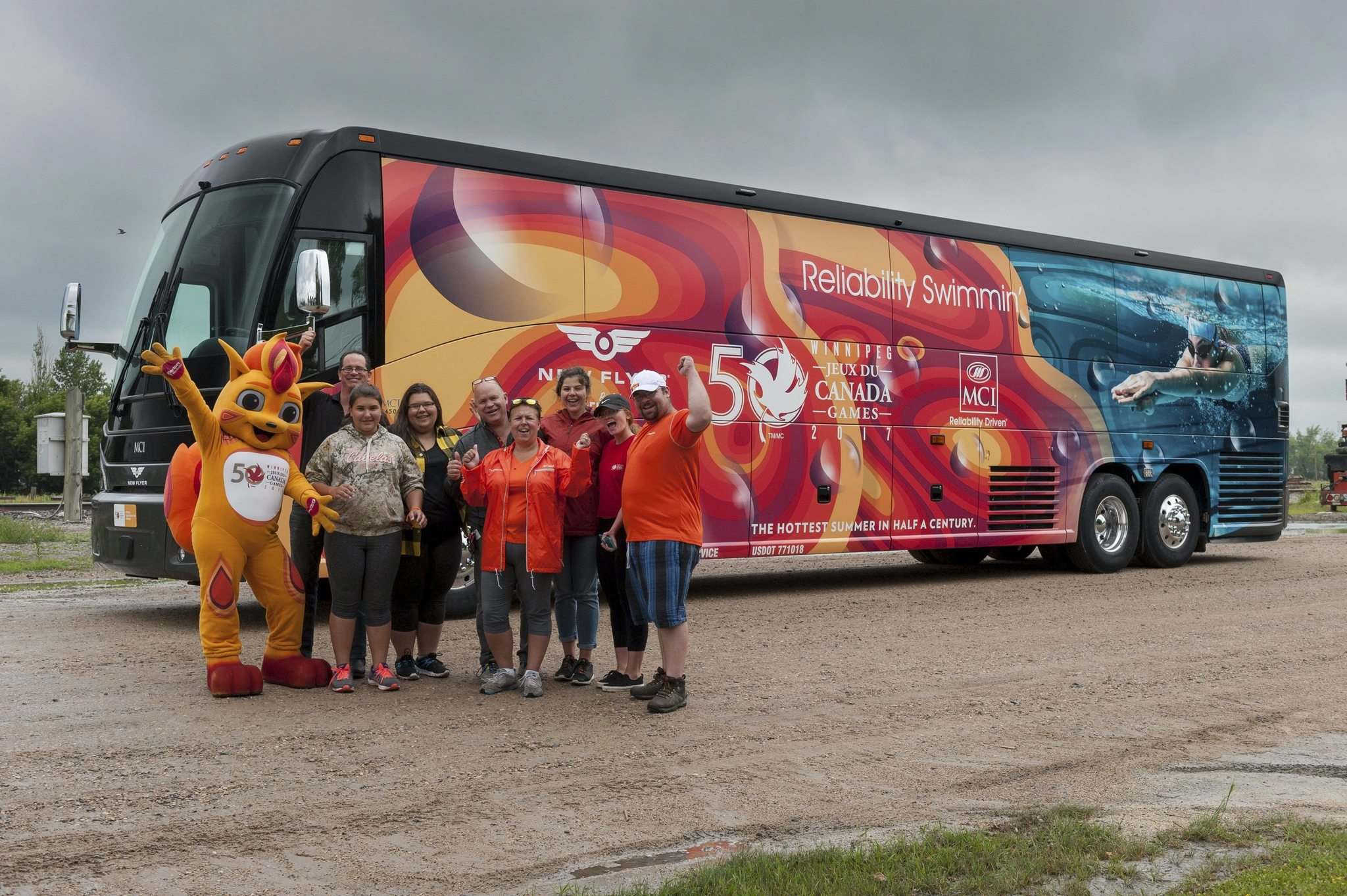 New Flyer Canada & MCI</p><p>Canada Summer Games mascot Niibin and volunteers stand in front of the coach transporting the official torch bearer team during the final leg of the torch relay. The Games begin Friday.</p></p>