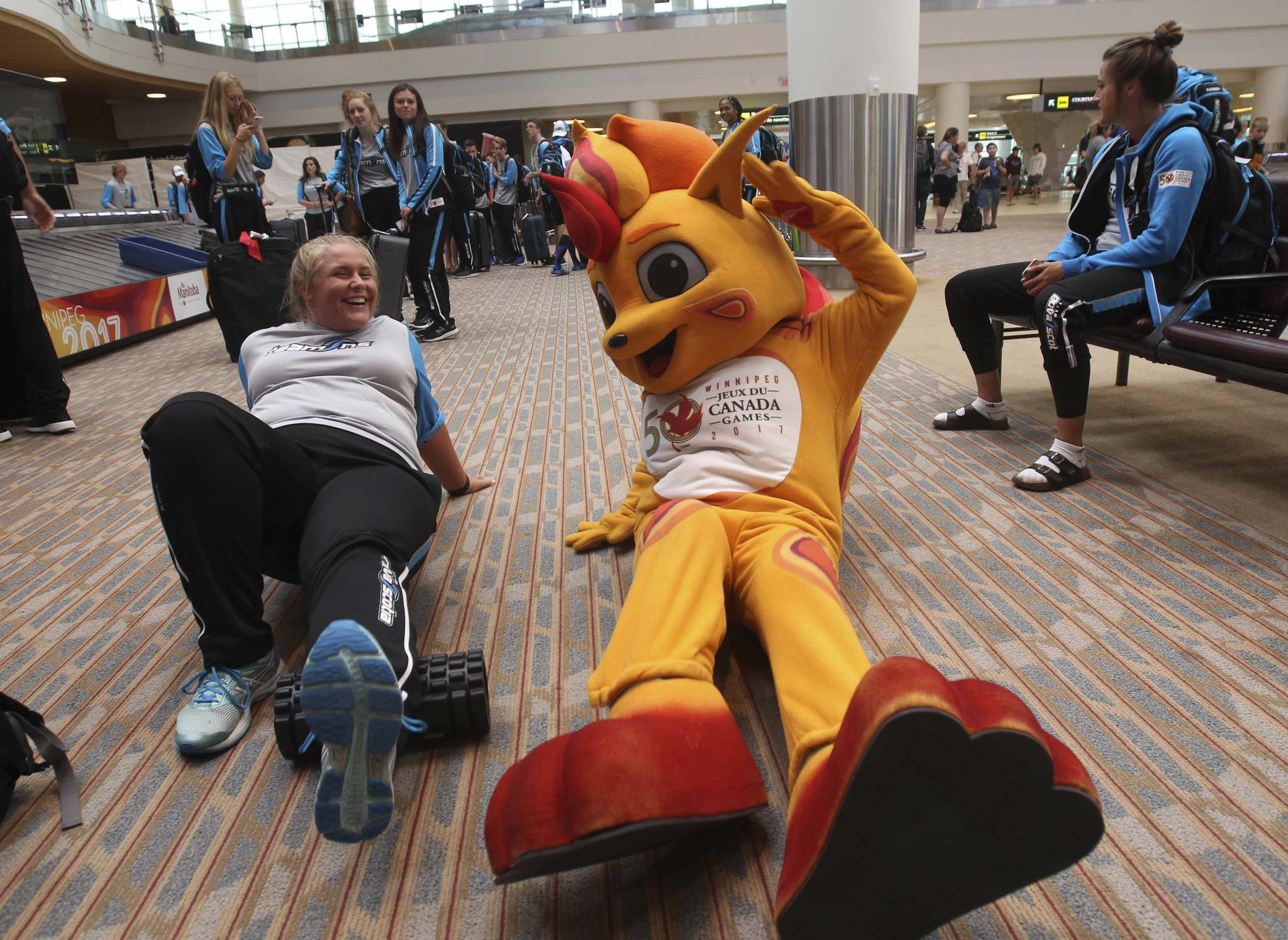 JOE BRYKSA / WINNIPEG FREE PRESS</p><p>Team Nova Scotia track and field athlete Taylor Stutely, 21, does some stretches with Canada games mascot Niibin as team Nova Scotia athletes arrive in Winnipeg.</p>
