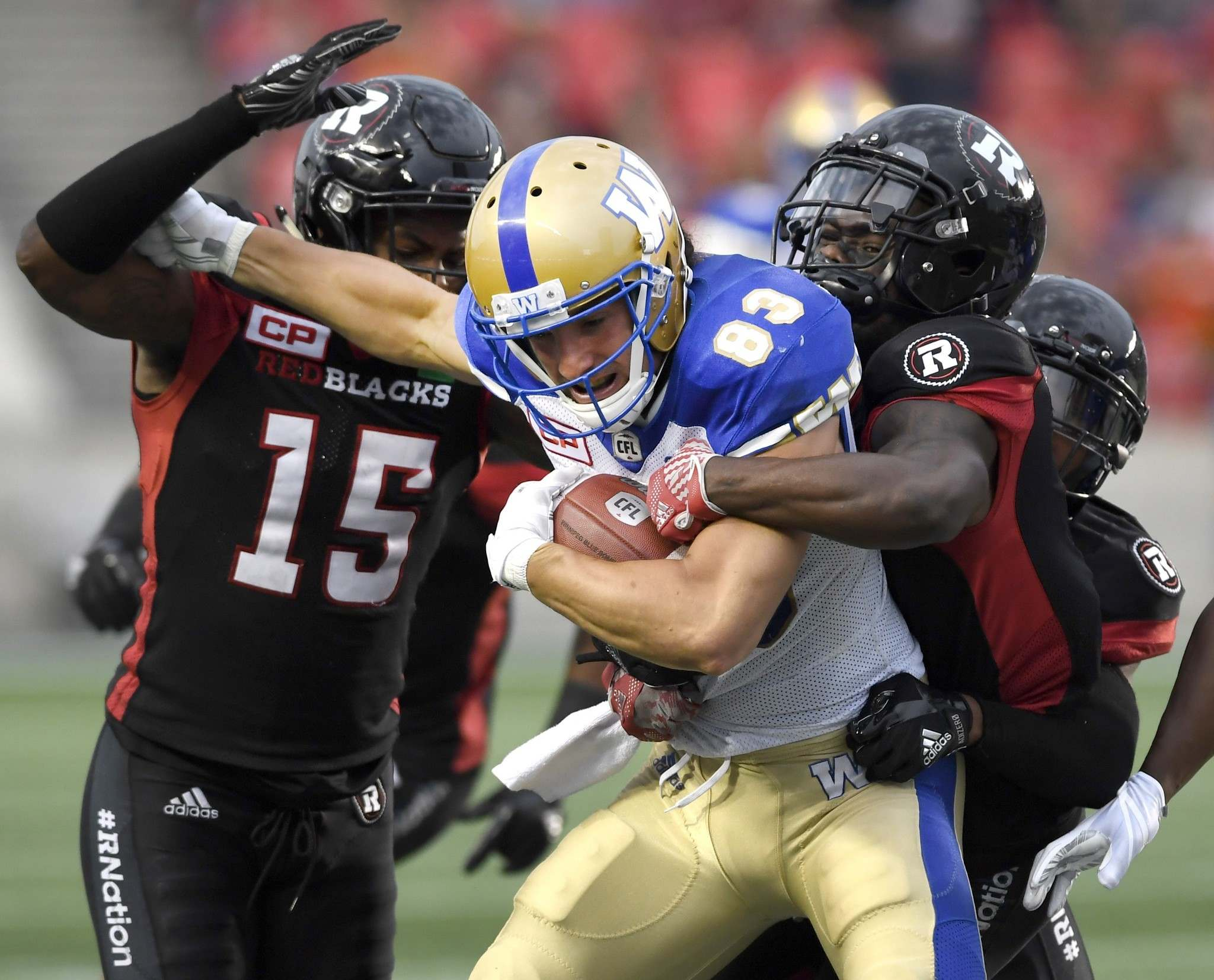 Bombers receiver Julian Feoli-Gudino fights to get past Redblacks defenders Keelan Johnson (left) and Jerrell Gavins Friday in Ottawa.