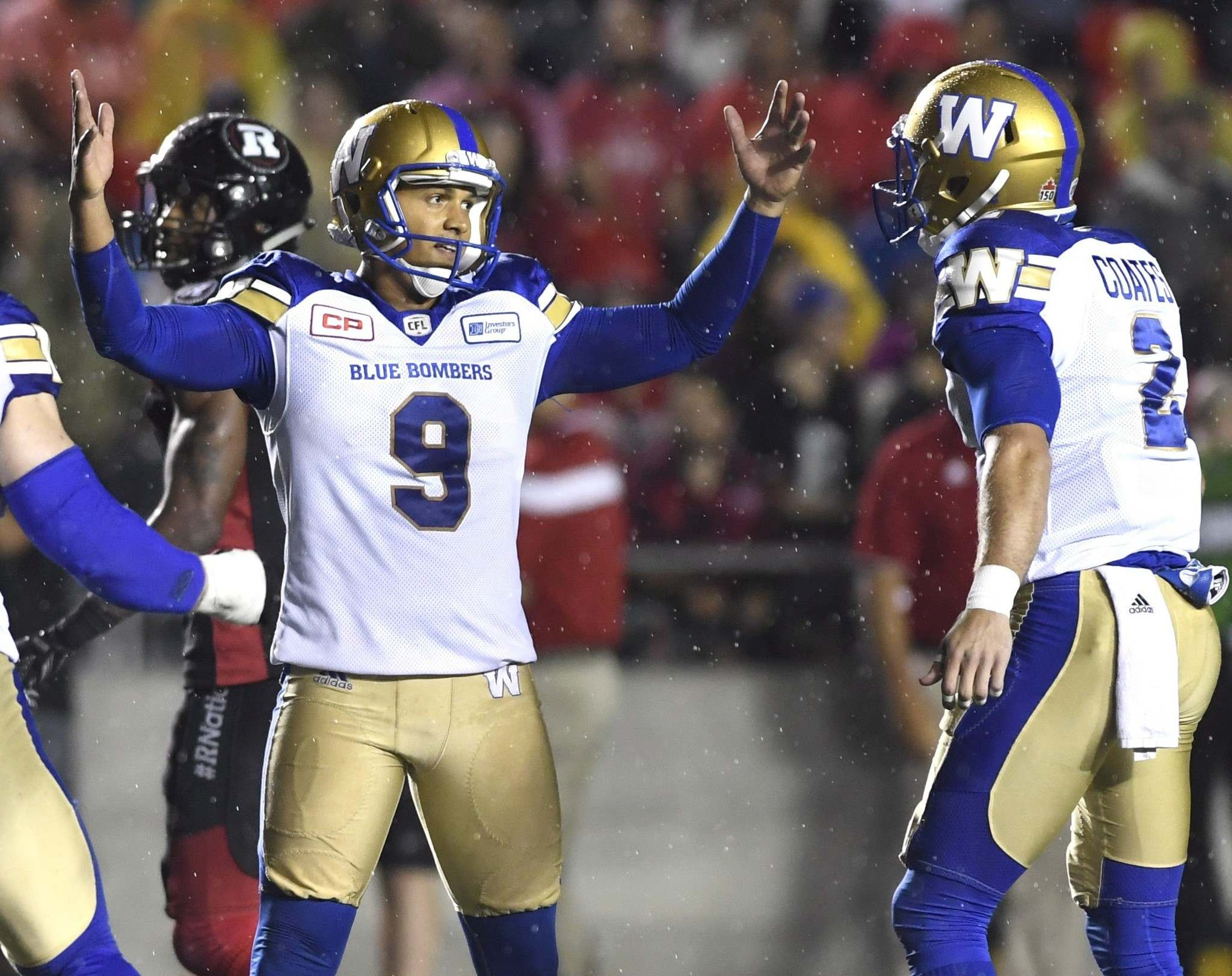 Bombers kicker Justin Medlock raises his hands as he celebrates his game winning field goal against the Ottawa Redblacks with teammate Matt Coates.