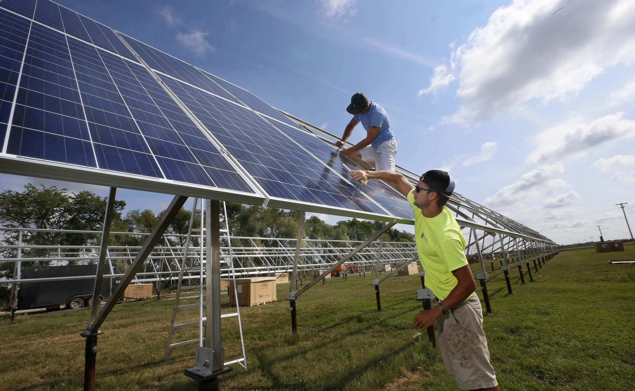 WAYNE GLOWACKI / WINNIPEG FREE PRESS</p><p>Bradly Becker (in foreground) and Tyson Kadynuik place a solar panel on Hans Gorter&rsquo;s dairy farm near Otterburne, Man. Above left, the group shows off the size of the panels.</p>
