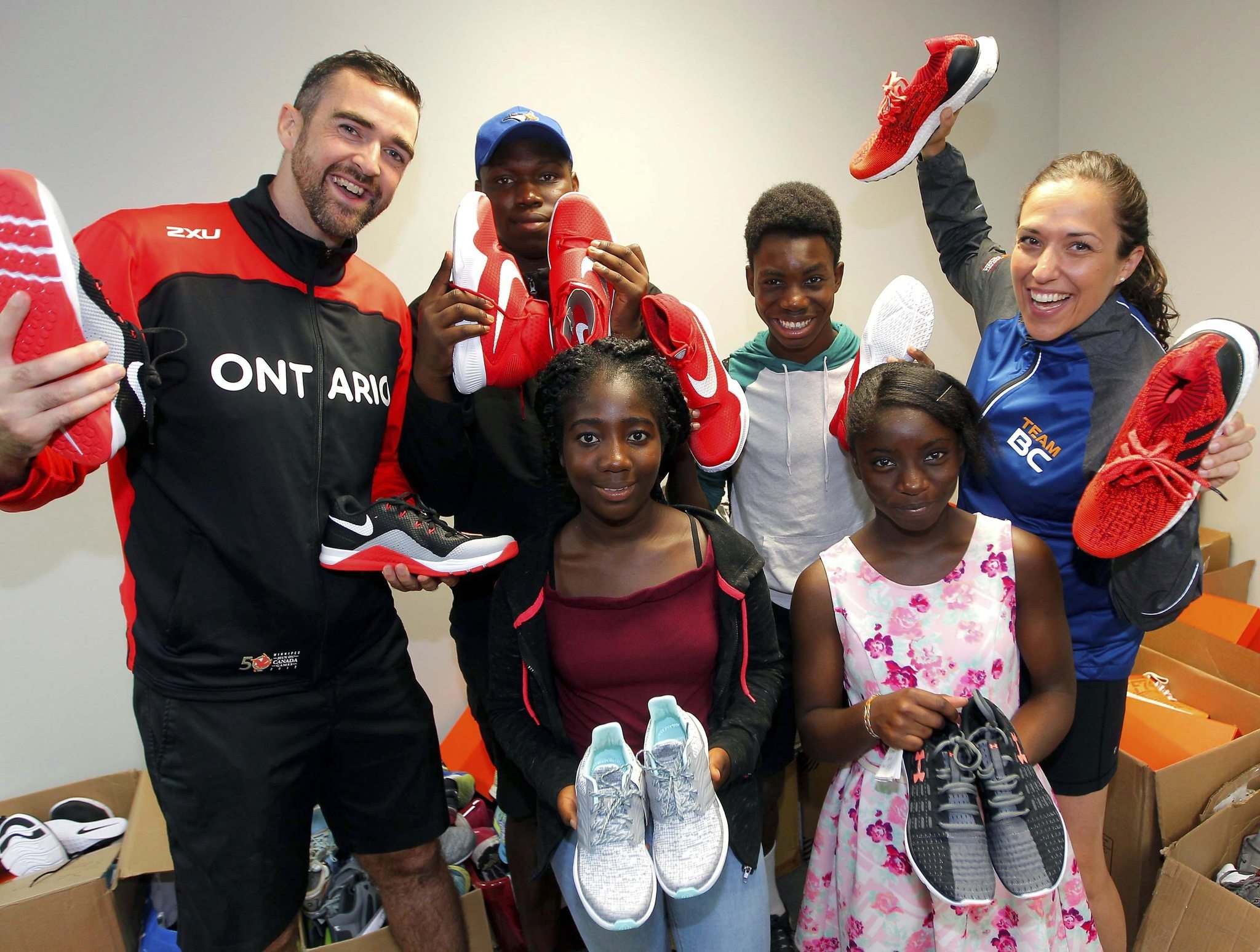 BORIS MINKEVICH / WINNIPEG FREE PRESS</p><p>Ontario's Nick Snow (left) and B.C.'s Michelle Collens (right) were on hand Thursday as their teams donated shoes to the Boys and Girls Club. Recipients include (back row from left) Emmanuel Olugbodi and Feranmi; (front row from left) Faith Odunayo, 14, and Dupe Abajesude, 11.</p></p>