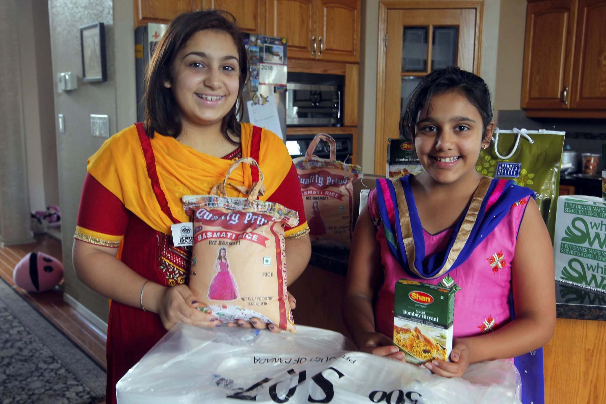 BORIS MINKEVICH / WINNIPEG FREE PRESS</p><p>Sisters Simryn (left),15, and Jasmyn Singh,11, will fill more than 600 containers and hand out the food at the Rockin&rsquo; the Village concert.</p>