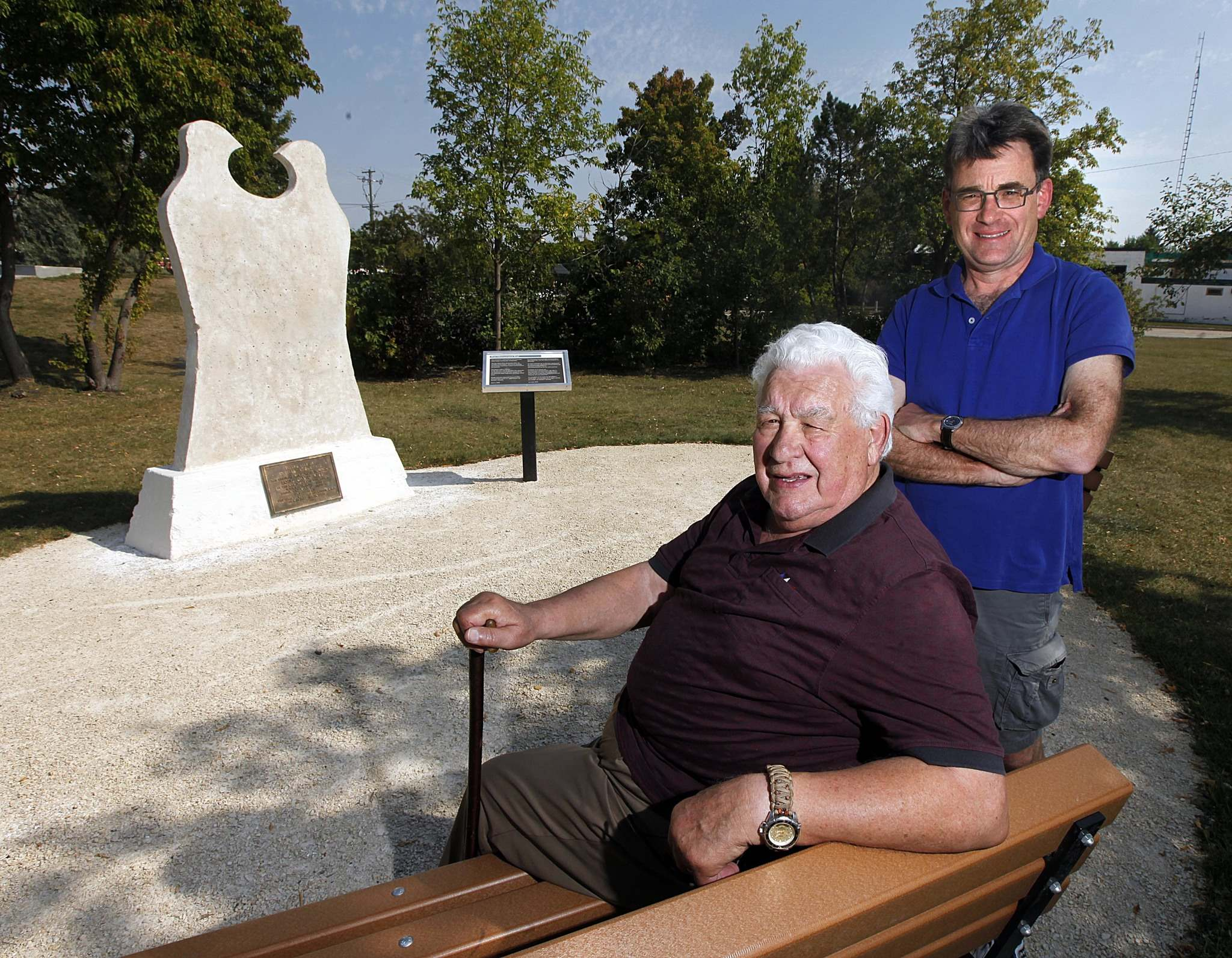 <p>Former city counselor and Elder with the Union Nationale Metisse, Guy Savoie, left and current city counselor Brian Mayes pose beside a repositioned and rejuvinated statue commemorating Louis Riel near St Annes Rd and Meadowood Ave.
