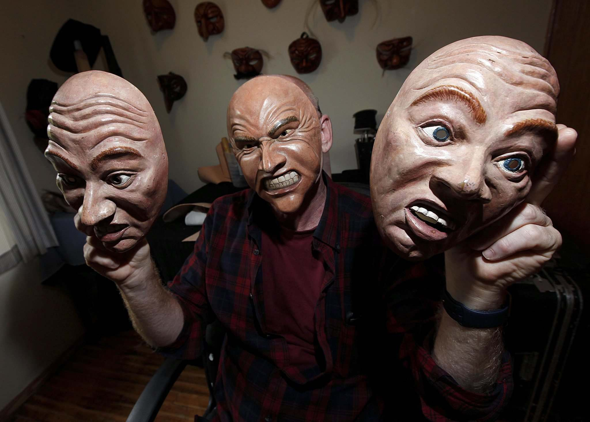 <p>Chris Sigurdson peers out from behind one of his Commedia dell&rsquo;arte masks modelled after his own face. He holds two more expressions.</p>