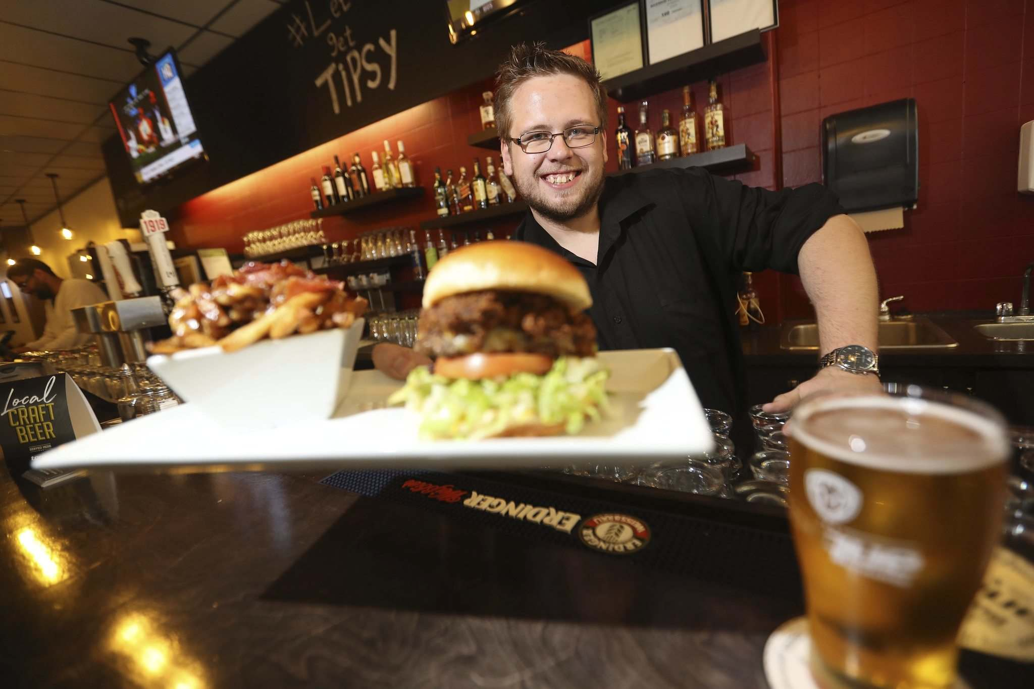 TREVOR HAGAN / WINNIPEG FREE PRESS</p><p>Josh Nesojednik, owner, holding the Bacon Poutine and the Winnipegger Burger at the Tipsy Cow.</p></p>