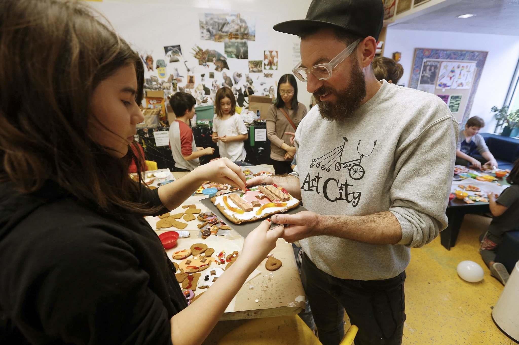 John Woods / Winnipeg Free Press</p><p>Eddie Ayoub, right, artistic director, helps children make haunted gingerbread houses at Art City in Winnipeg Monday.</p>